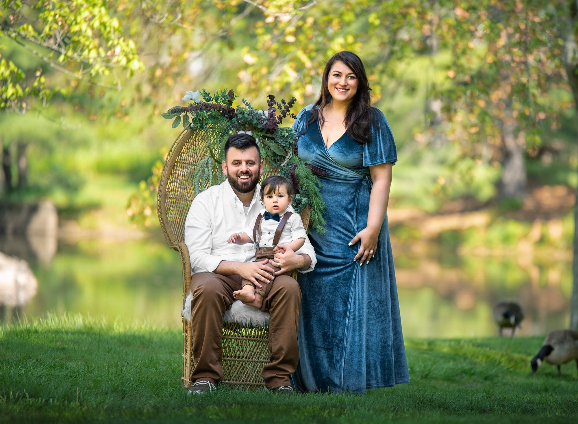 dad holding one year old boy sitting in his lap while sitting on a wicker chair in nature dressed up in greenery next to his wife