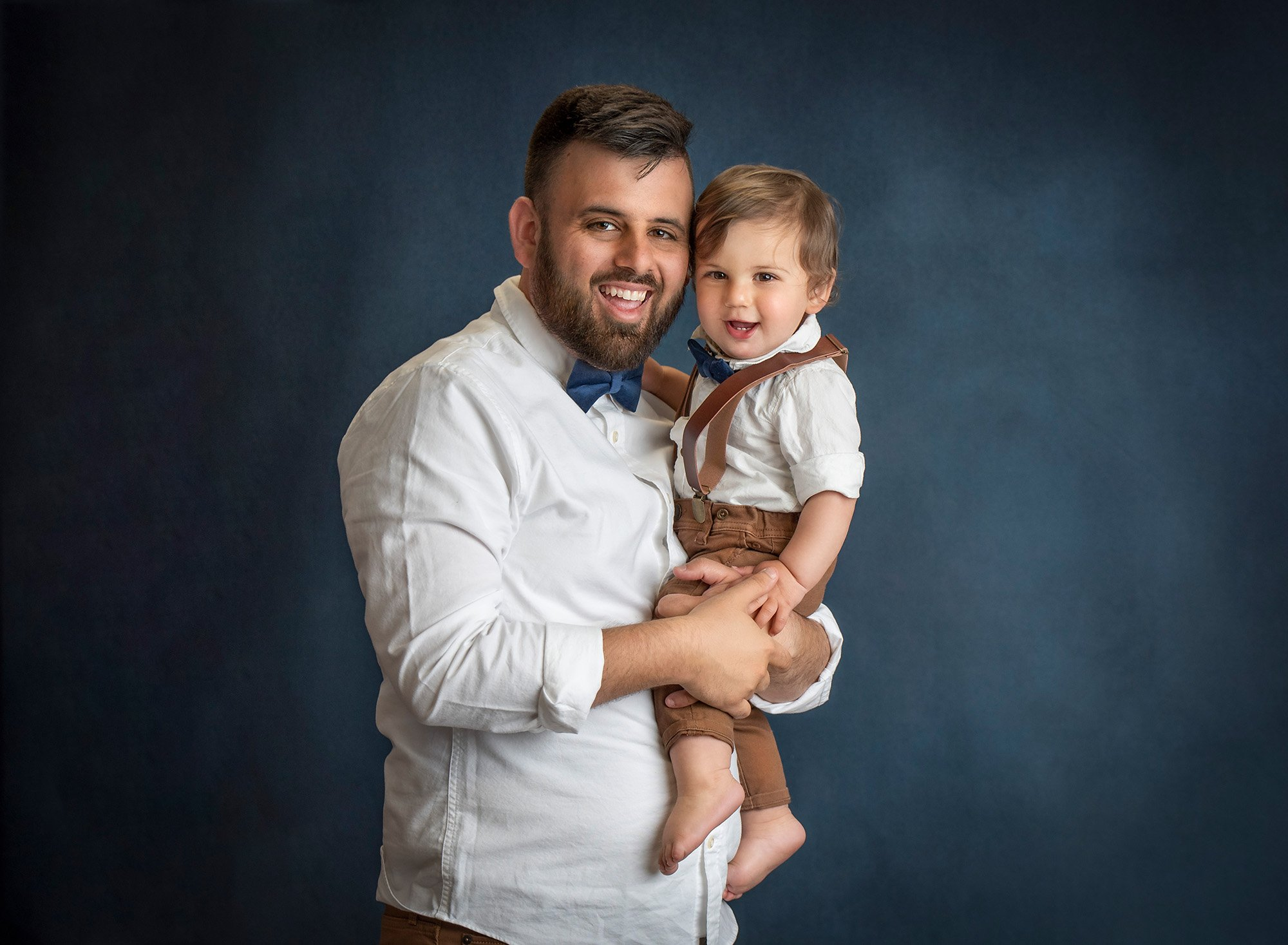 one year old boy in overalls smiling while being held by his dad on a blue background