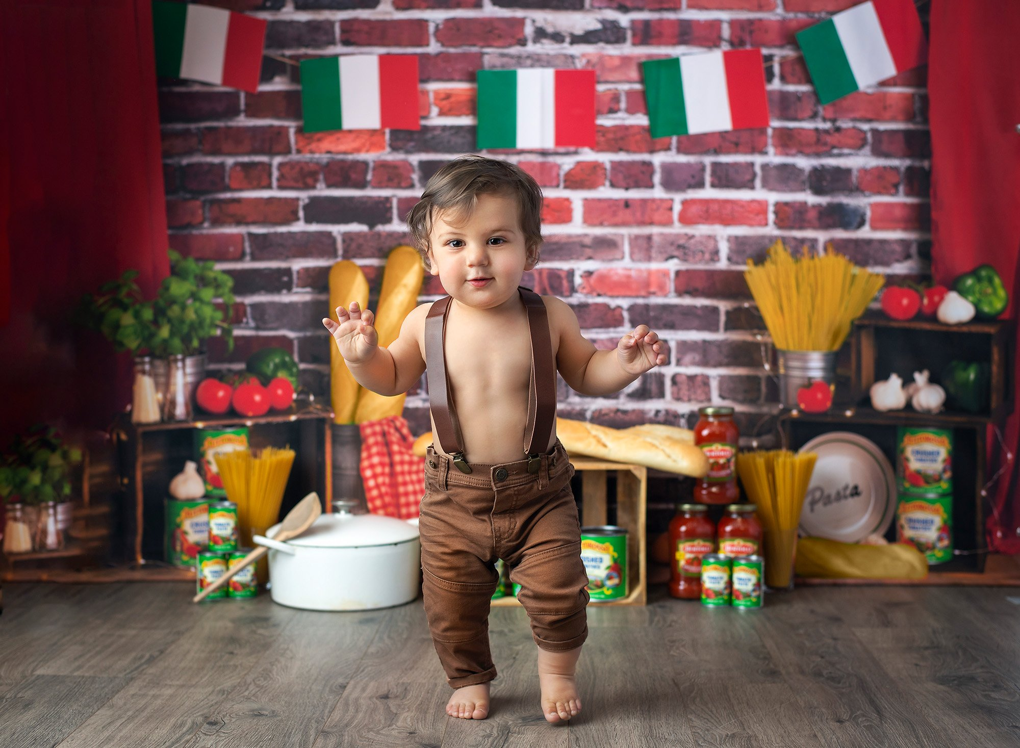 1 year baby photoshoot spaghetti smash one year old boy walking in overalls with Italian flags, Italian bread, pasta and jars of sauce in background