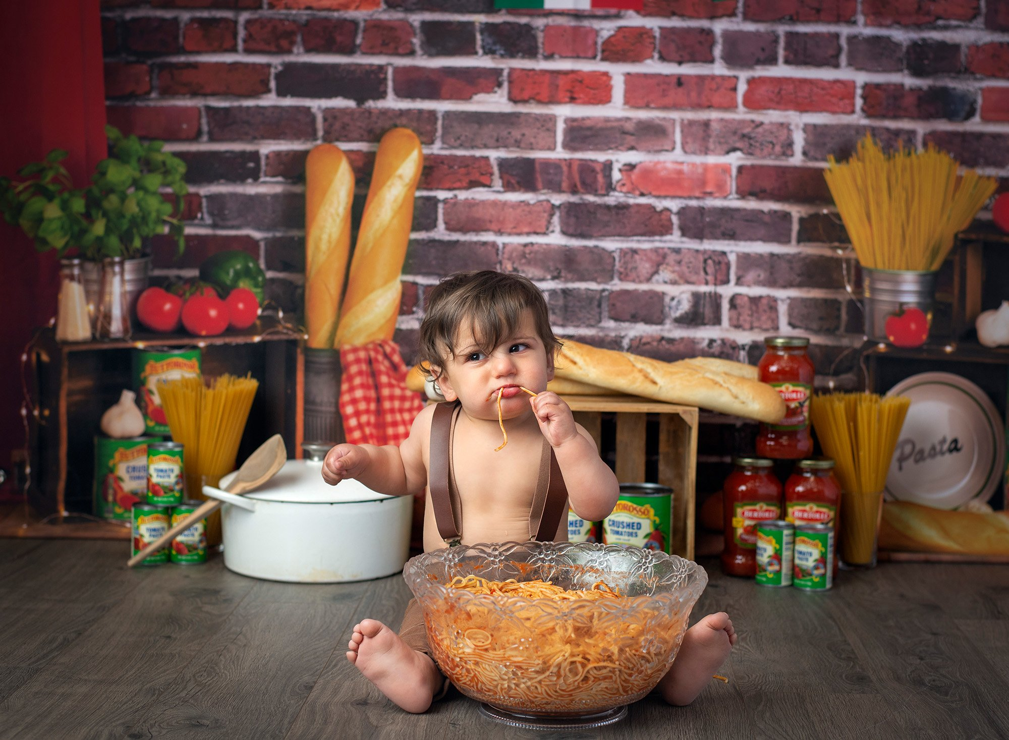 one year old boy eating spaghetti with Italian bread and jars of sauce in background