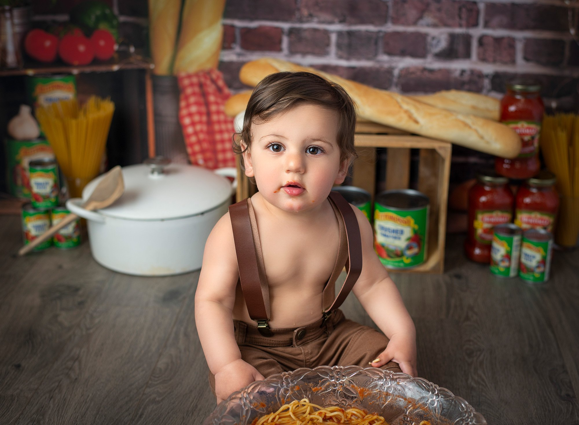one year old boy wearing overalls with Italian bread and jars of sauce in the background