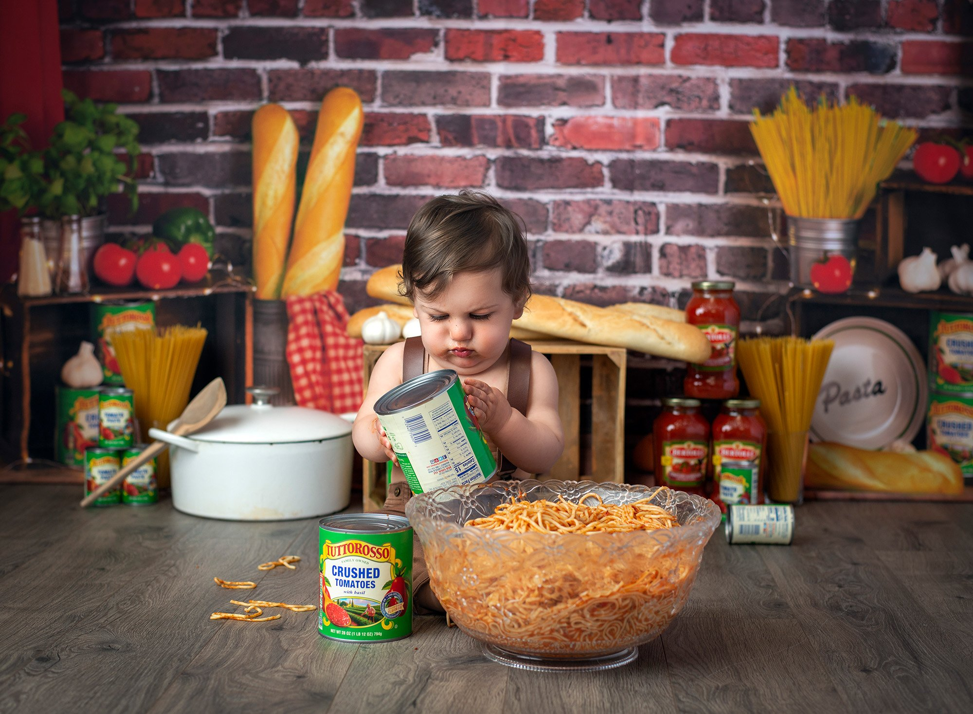 1 year baby photoshoot spaghetti smash one year old boy playing with tomato cans while surrounded by pasta and sauce jars on a brick background