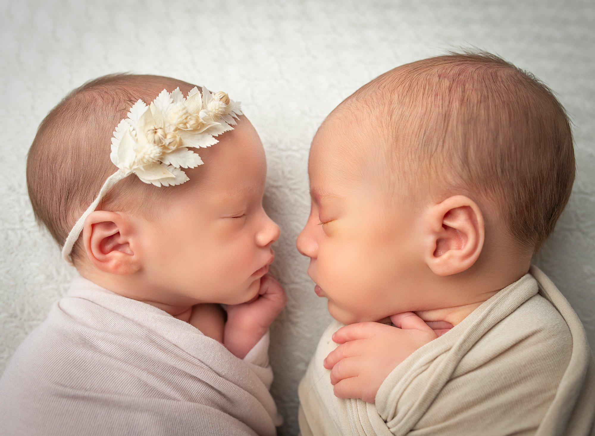 newborn twin girl and boy sound asleep facing each other swaddled in wraps