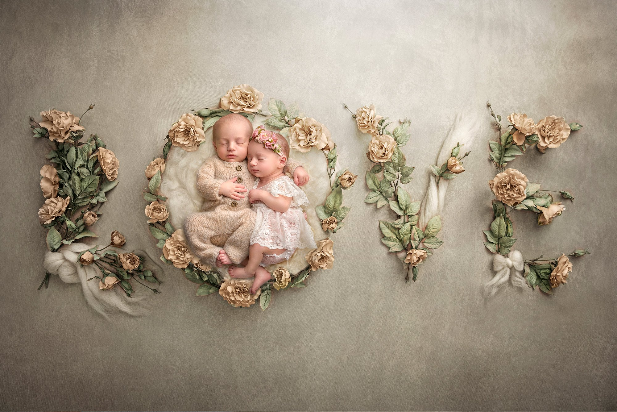 Twins newborn photography sweet newborn twins asleep on a grey background spelling out the word LOVE in flowers and bows