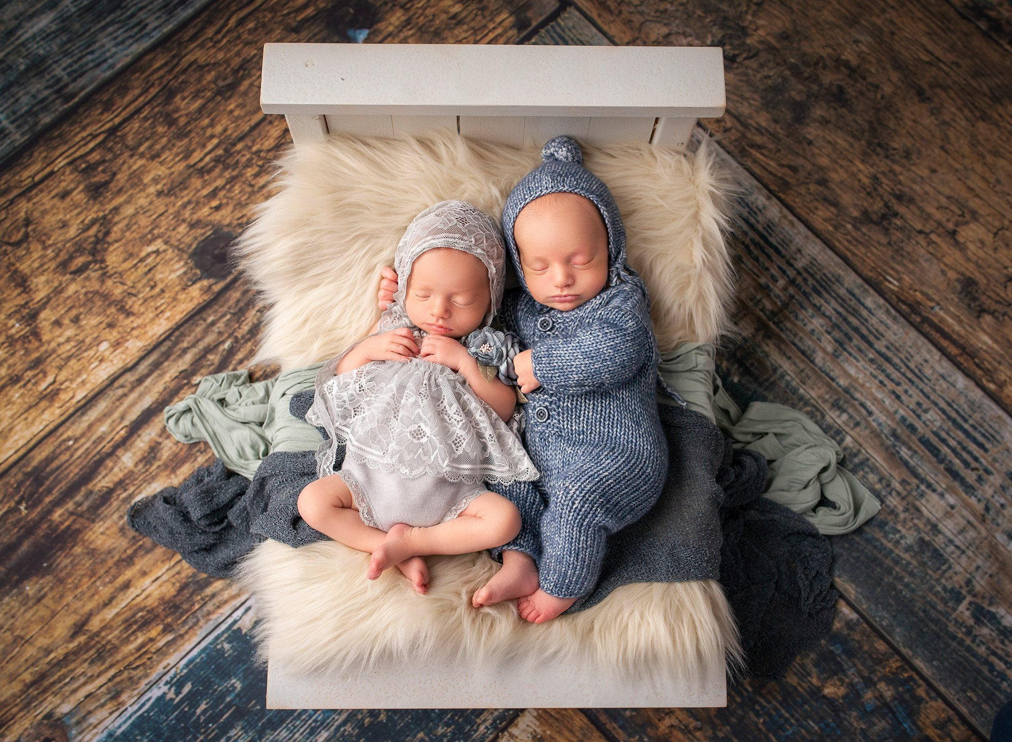 Twins newborn photography newborn twin boy and girl laying asleep next to each other on a miniature white bed with blankets
