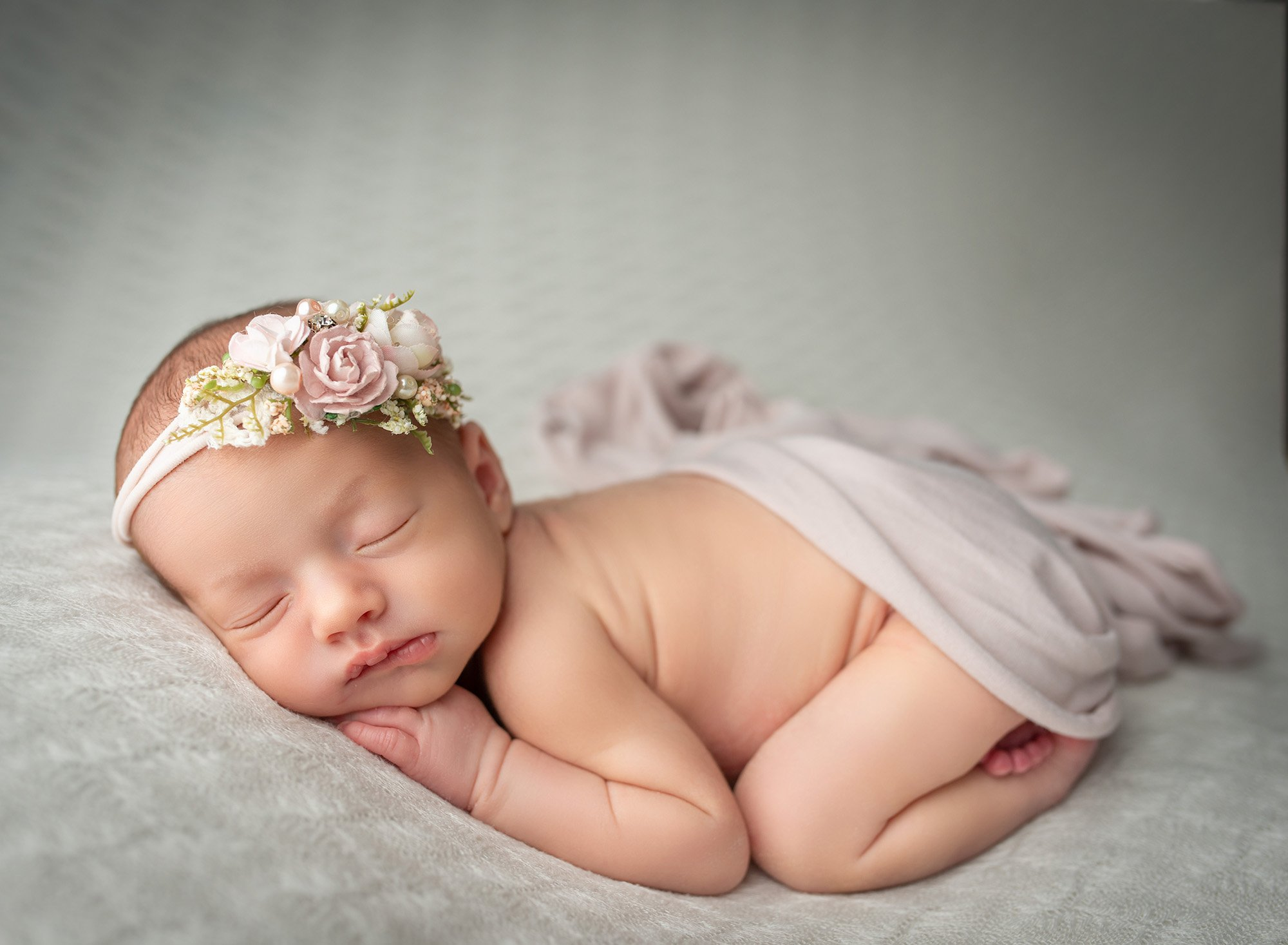 newborn baby girl laying naked with floral headband on white blanket