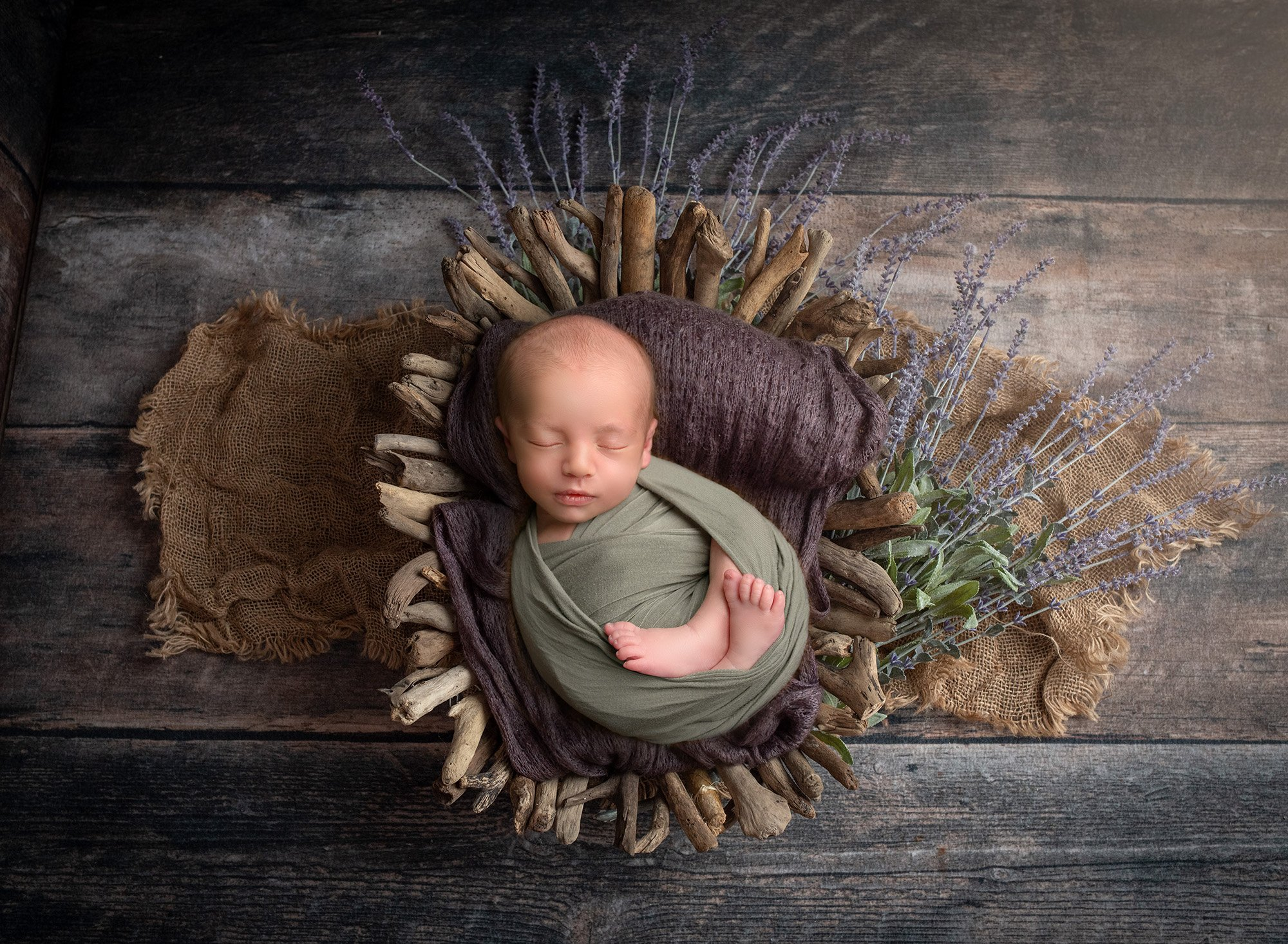 newborn baby boy swaddled in green laying in woodsy basket with lavender sprouting underneath