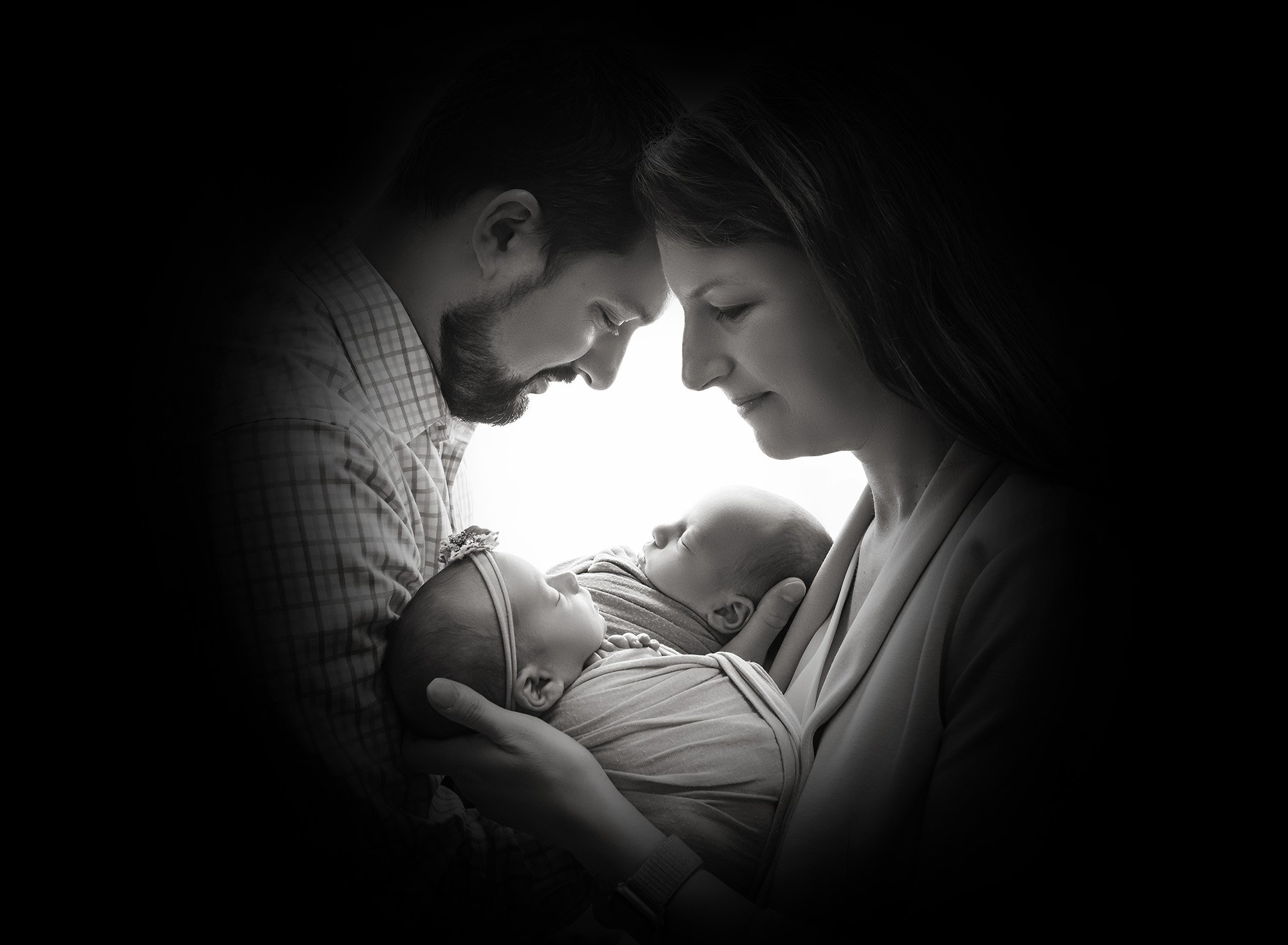 Twins newborn photography silhouette shadow of new parents face's while cradling their newborn baby boy and girl