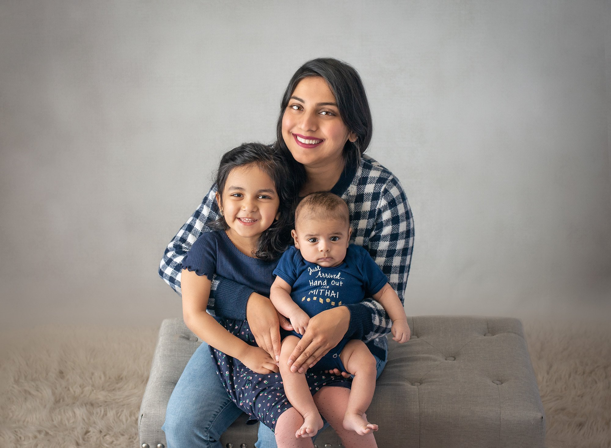 mom smiling holding young daughter and newborn baby boy all dressed in navy blue