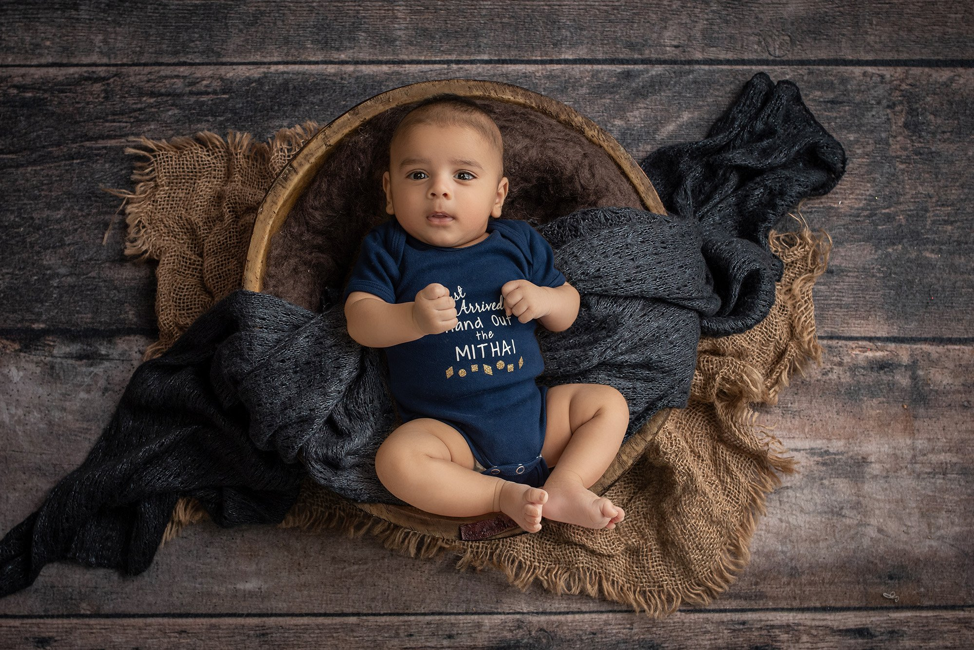 baby portraits 2 month old baby boy wearing navy blue onesie laying inside wooden bowl with blue and brown blankets