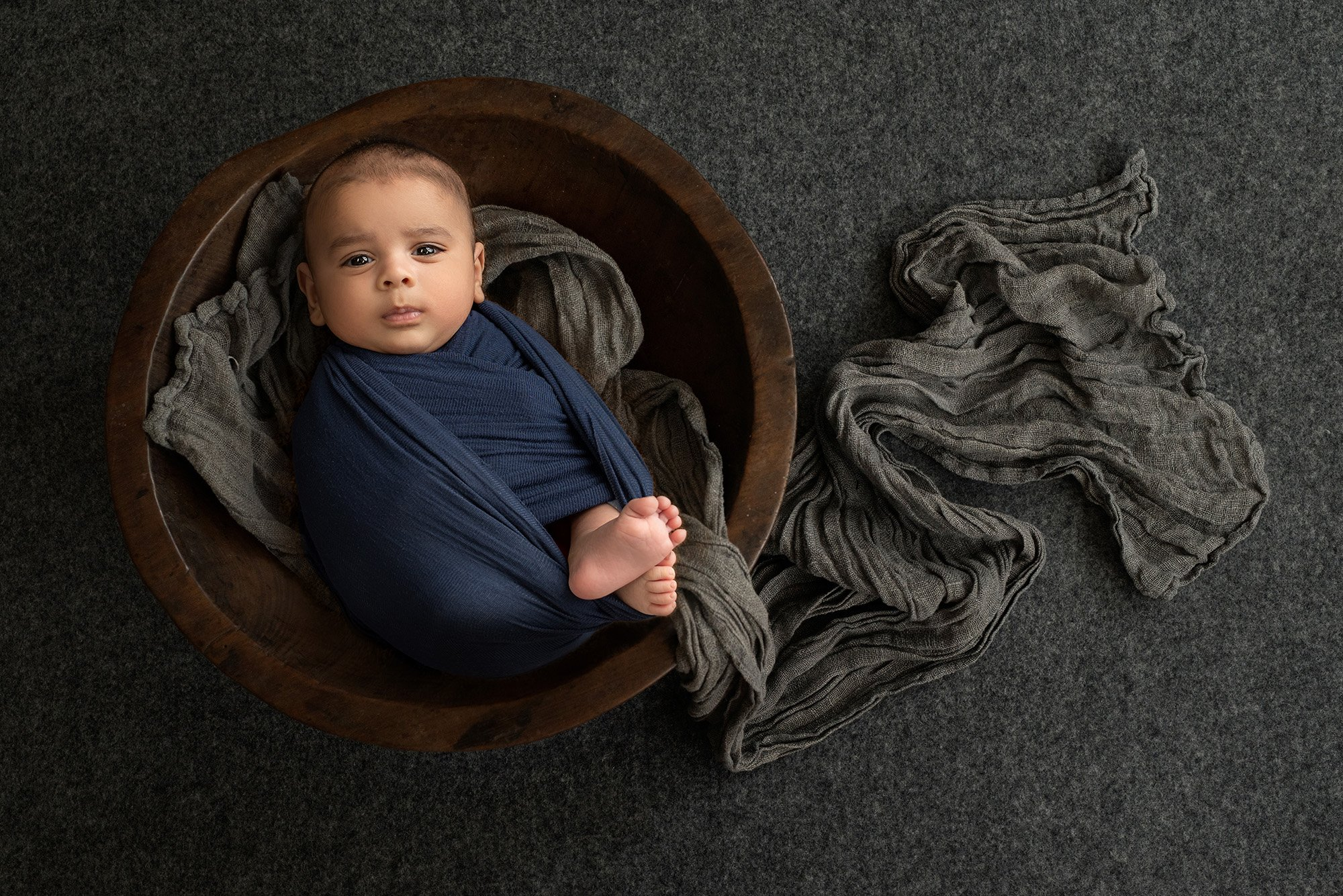 baby portraits newborn baby boy swaddled in blue laying on grey wrap inside wooden bowl