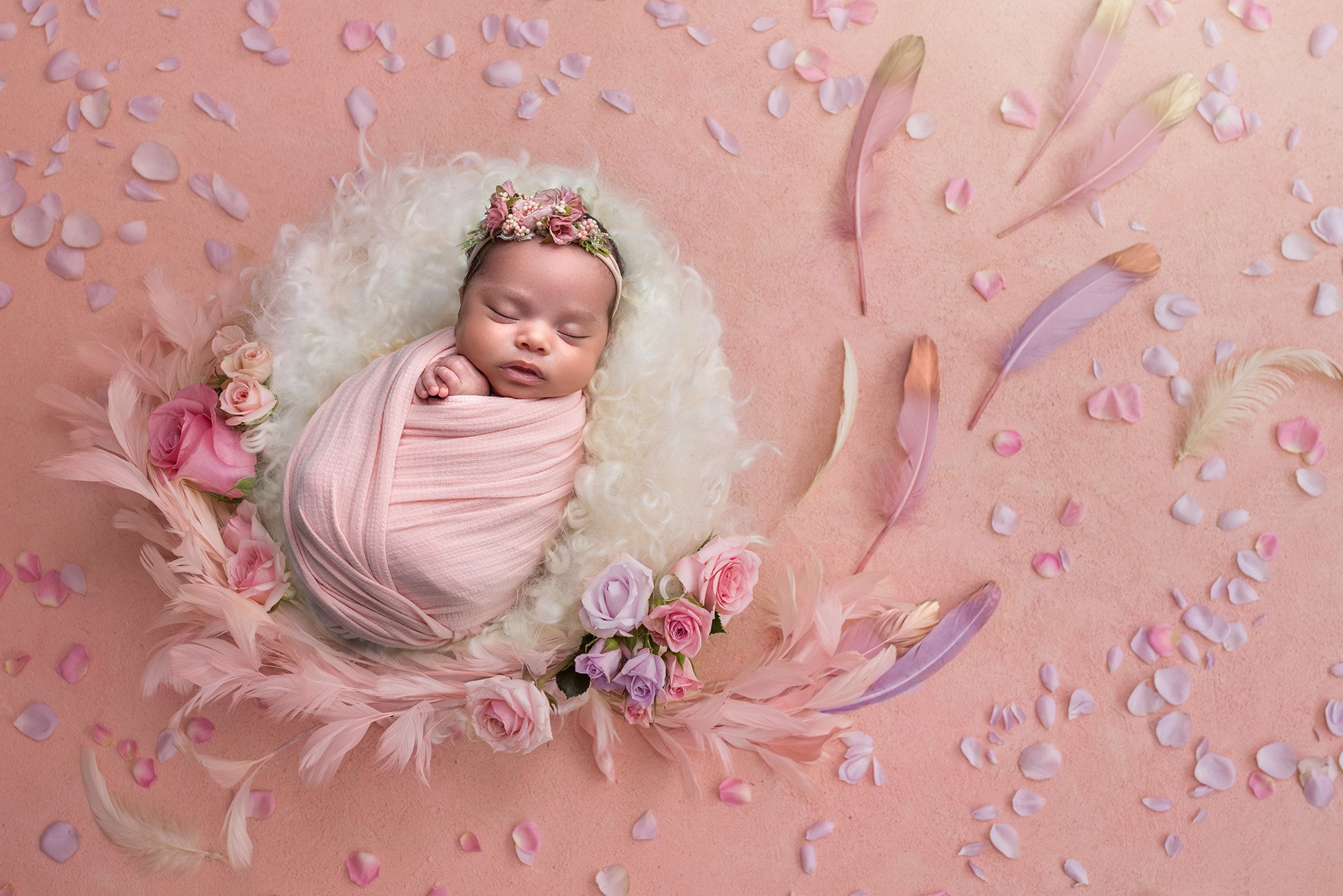 girly girl newborn photos newborn baby girl swaddled in pink sleeping on fuzzy blanket surrounded by feathers and flower petals