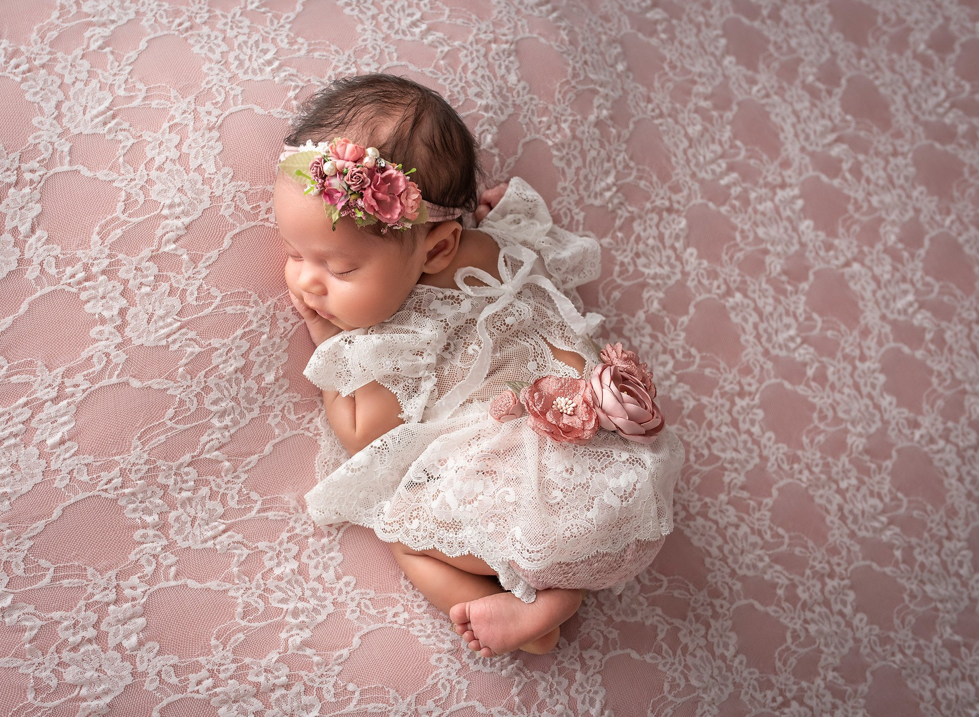 girly girl newborn photos newborn baby girl laying on stomach on top of pink lace wearing lace dress and pink floral headband