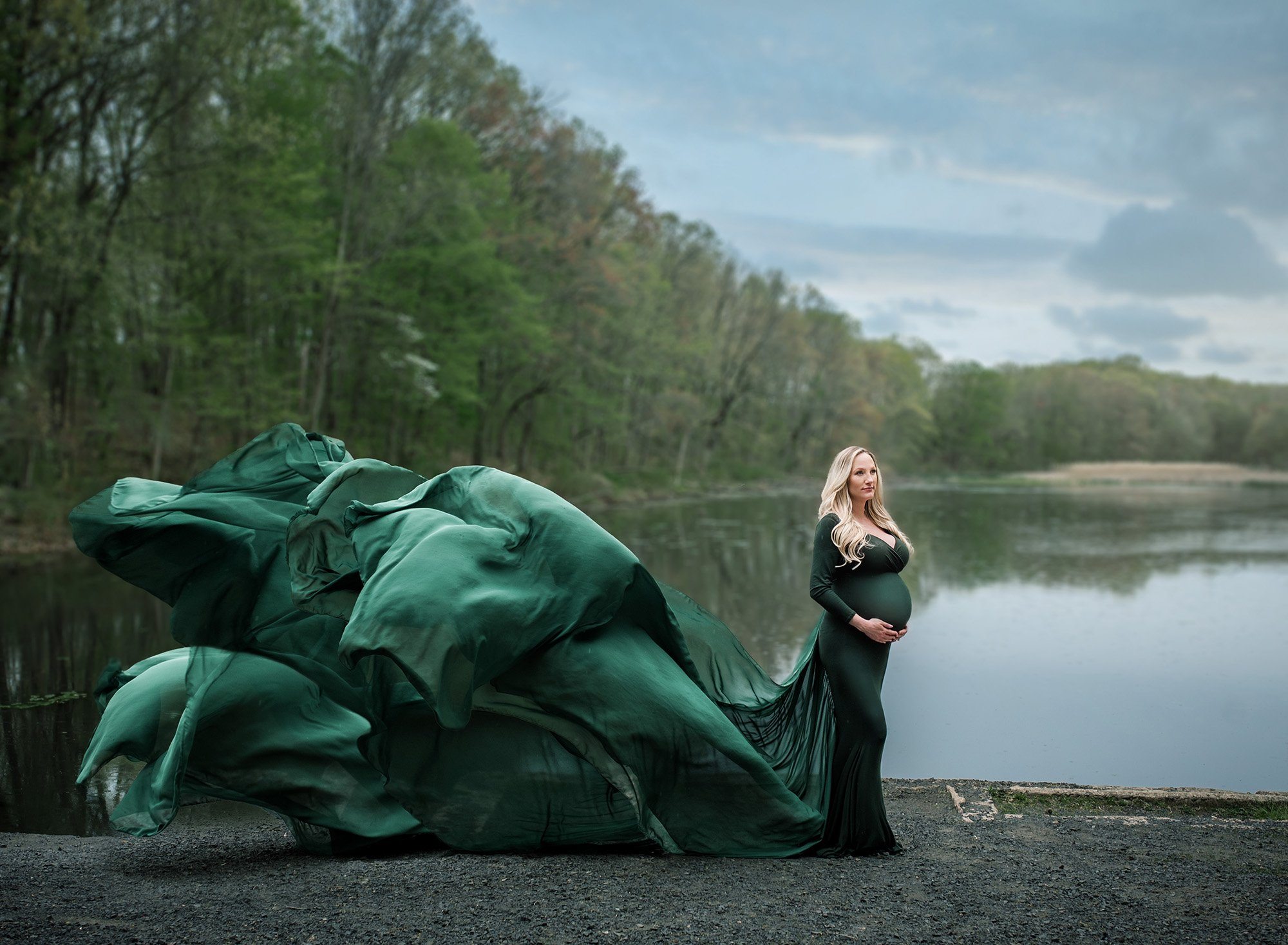 Connecticut Maternity Photographer Beautiful blonde woman wearing a gorgeous flowing emerald green gown I'm front of a lake on a stormy day
