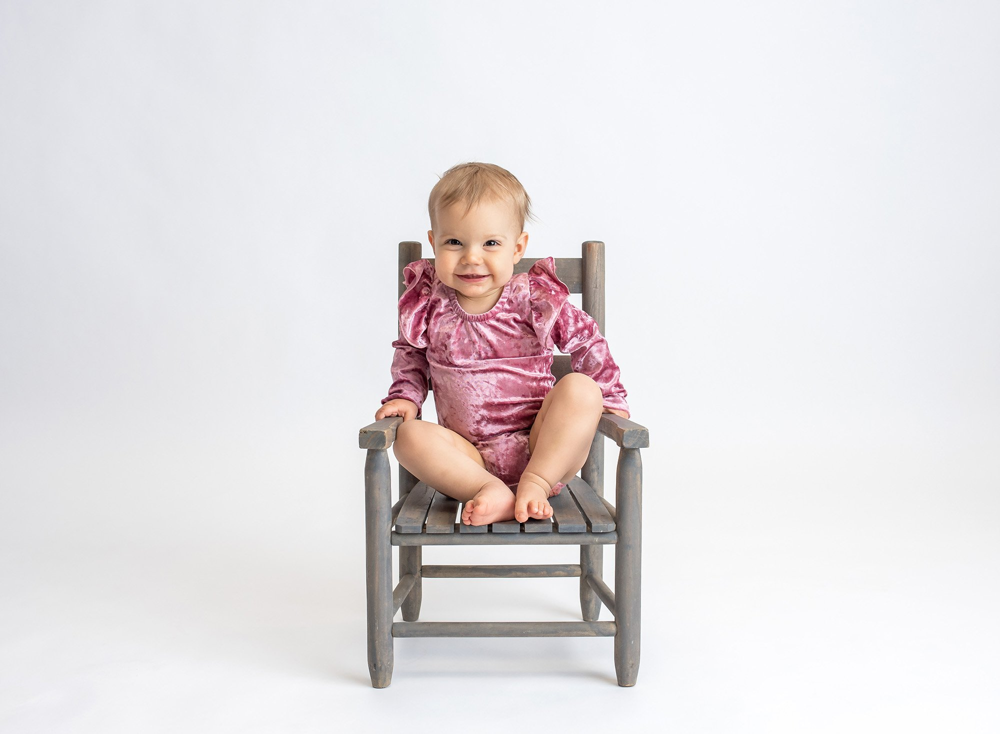 blonde one year old girl wearing pink velvet body suit sitting on rustic chair with white backdrop