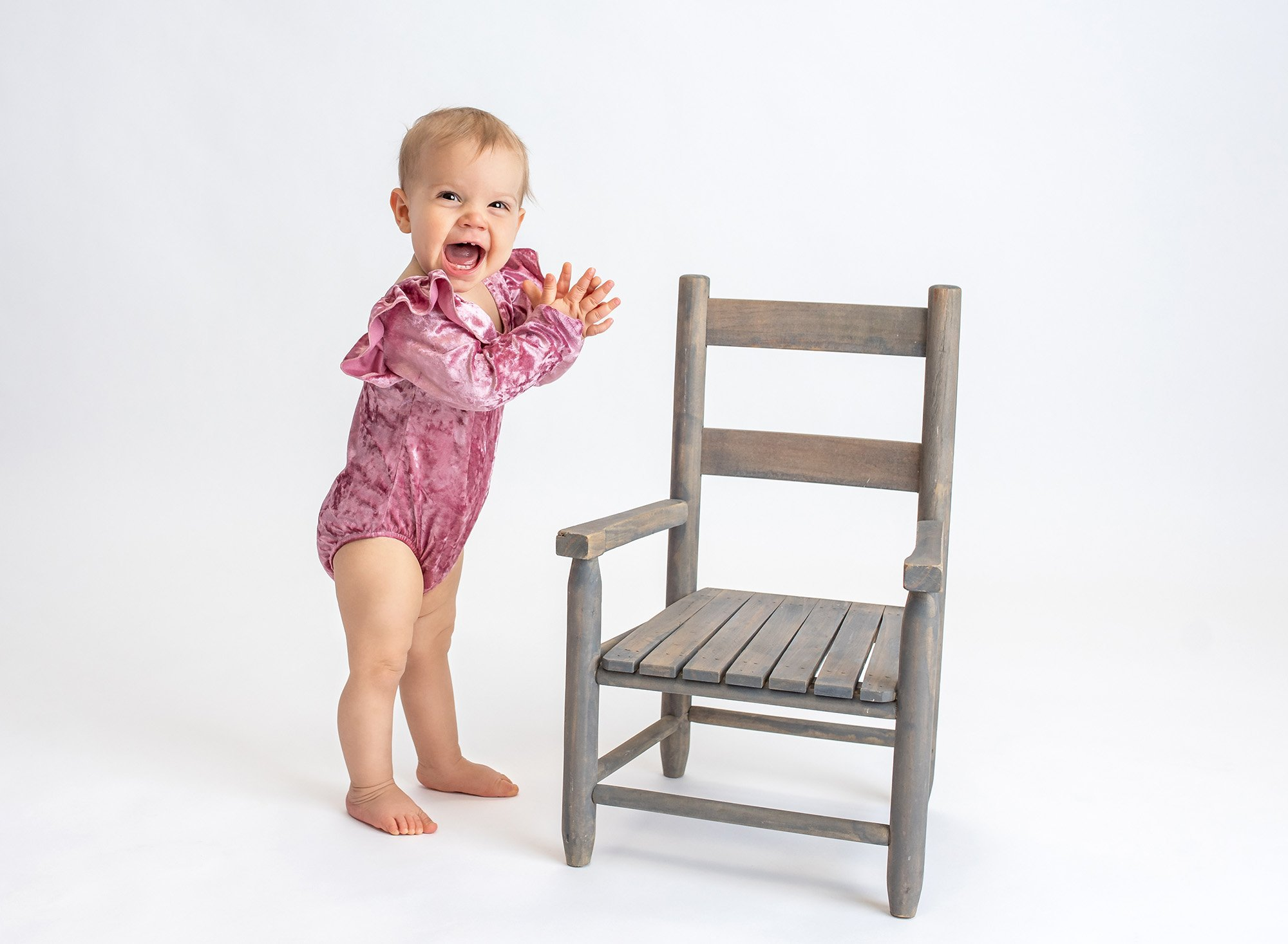 1 year baby photoshoot one year old girl laughing and clapping wearing a pink velvet ruffled body suit with rustic chair