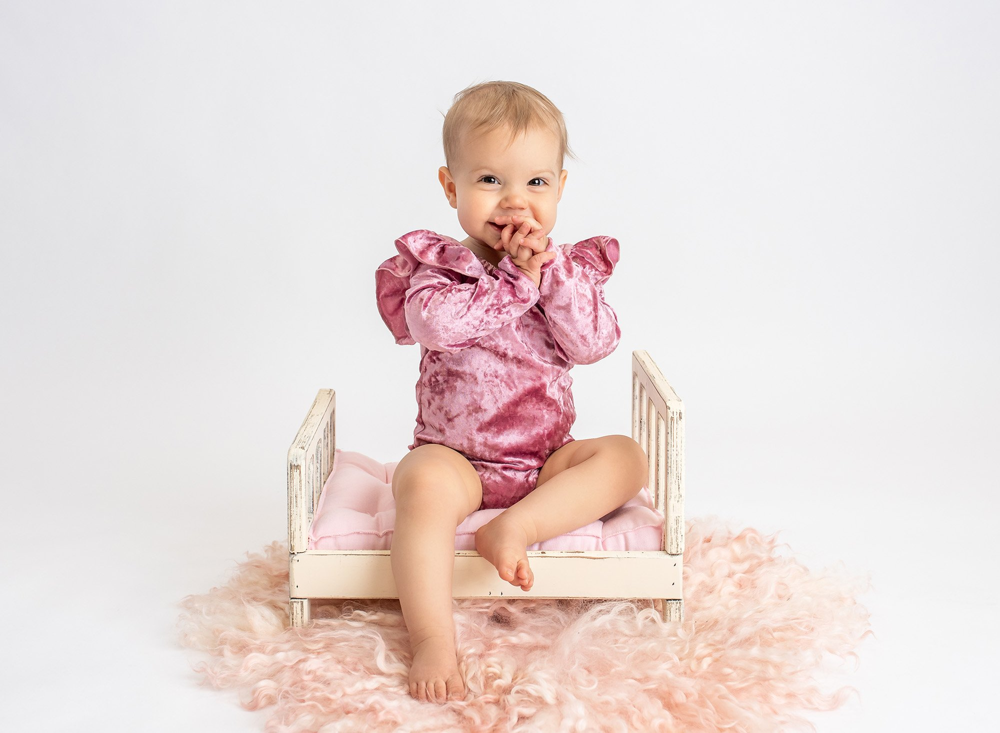 one year old girl wearing pink velvet ruffled bodysuit sitting on top of miniature white shabby bed with pink cushion