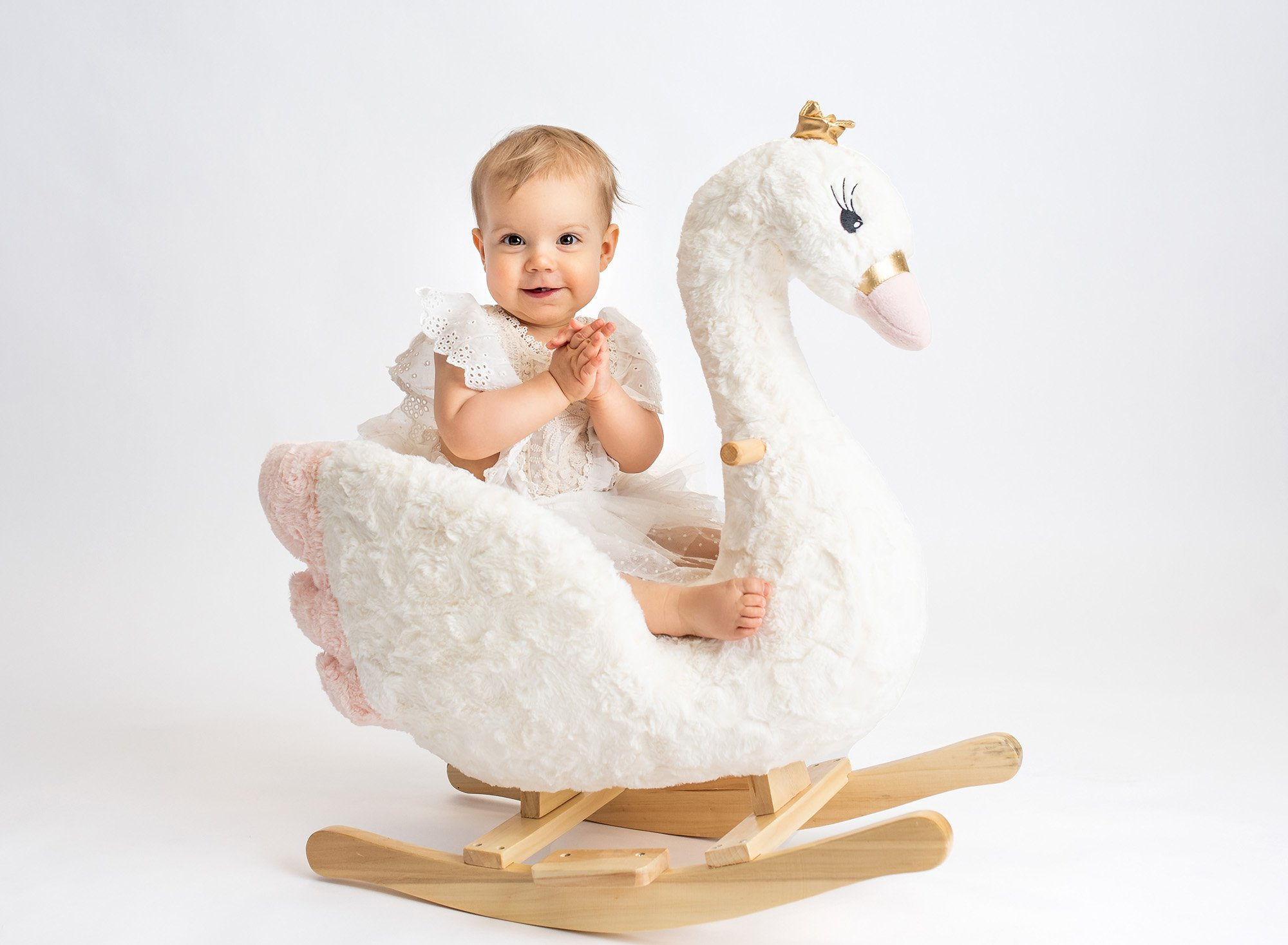 1 year baby photoshoot one year old girl wearing white lace dress sitting on swan rocker with white backdrop
