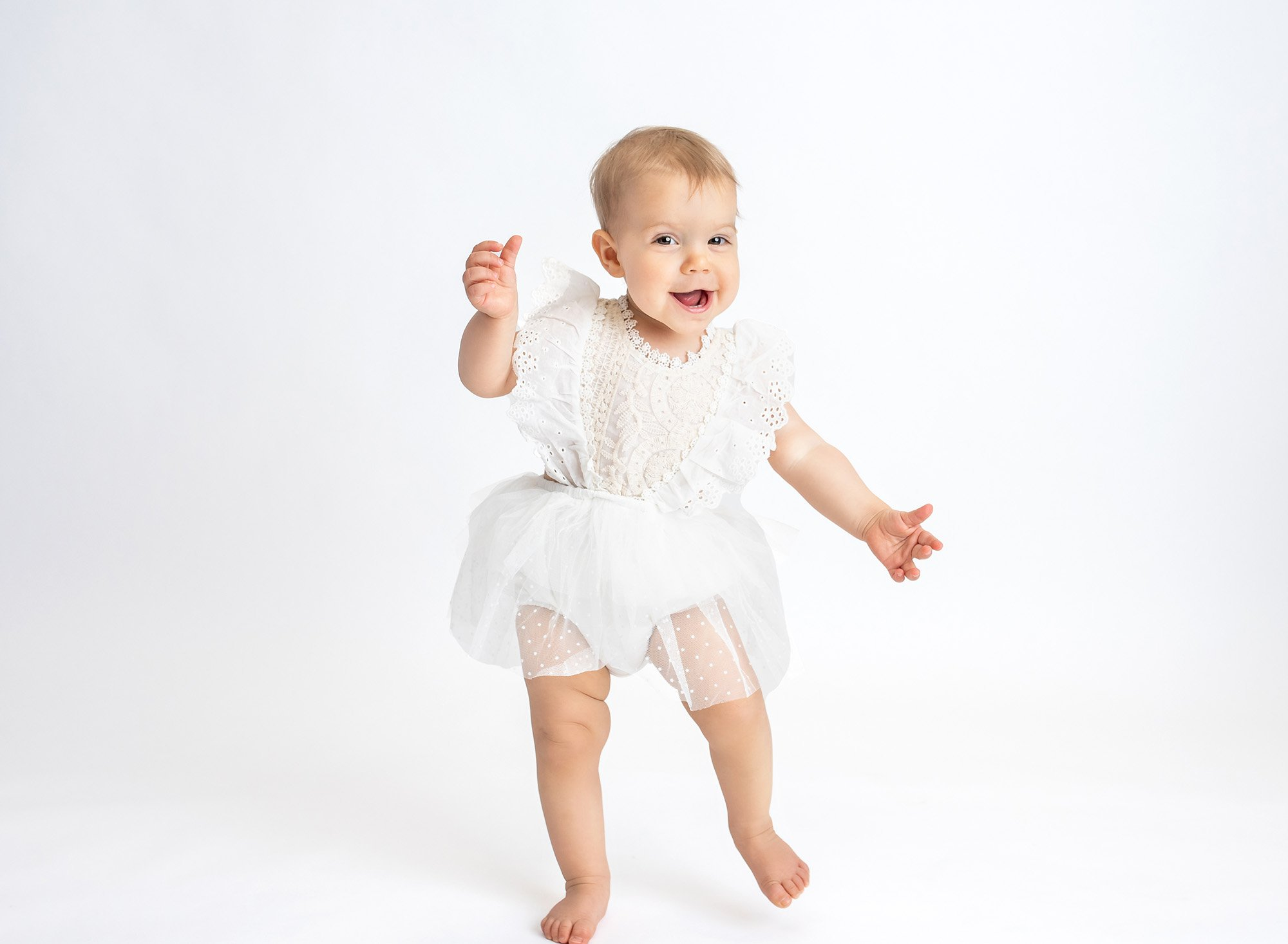 brown eyed one year old girl wearing white lace dress smiling and walking with white backdrop