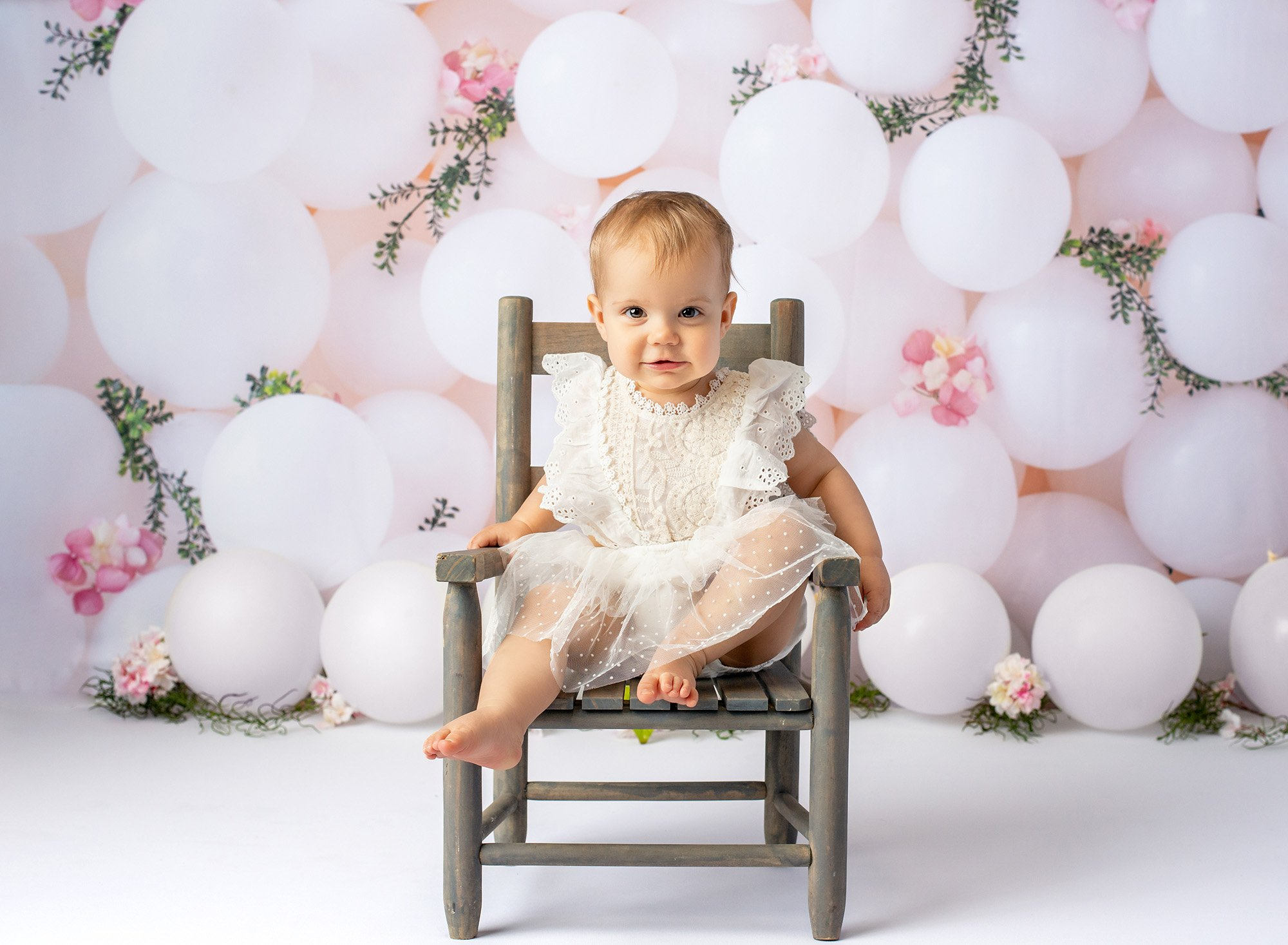1 year baby photoshoot brown eyed one year old girl wearing white lace dress sitting on rustic chair with white balloons in background