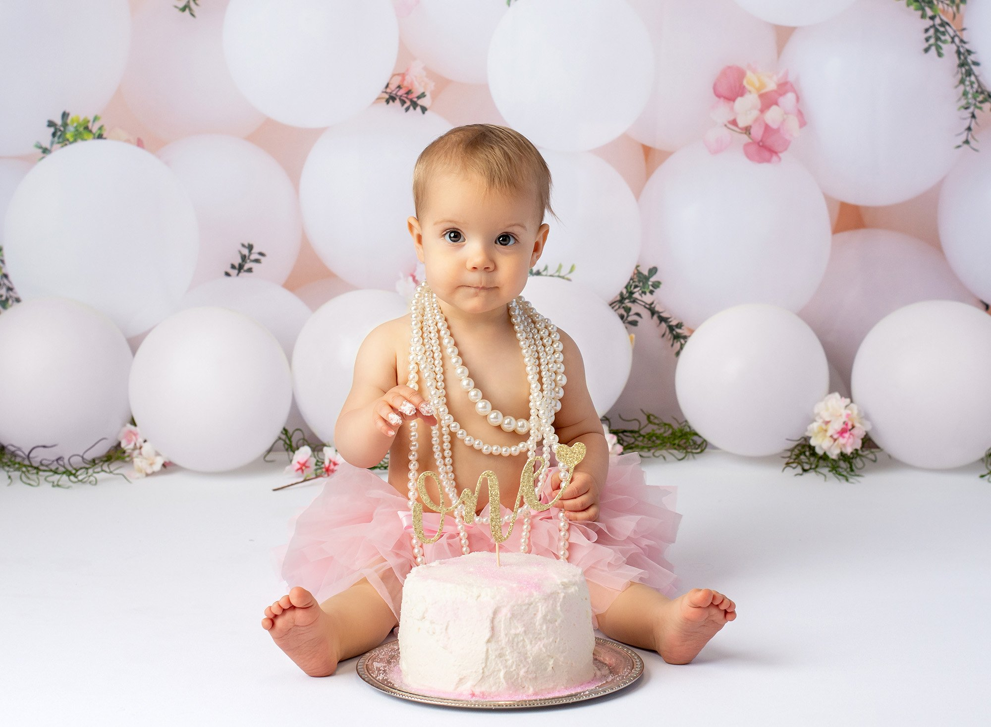 baby girl wearing layered pearl necklace and pink tutu sitting in front of cake with gold glitter ONE sign with white balloons in background and frosting on fingers