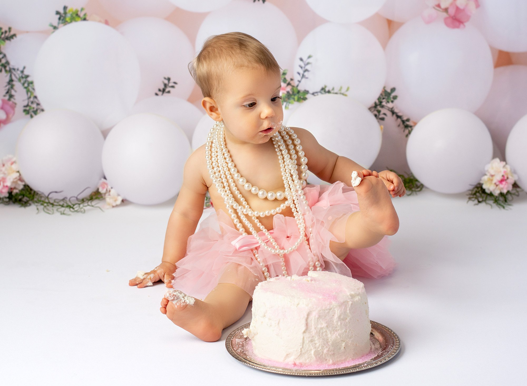 1 year baby photoshoot baby girl wearing layered pearl necklace and pink tutu sitting in front of cake holding up foot with frosting on toe with white balloons in background