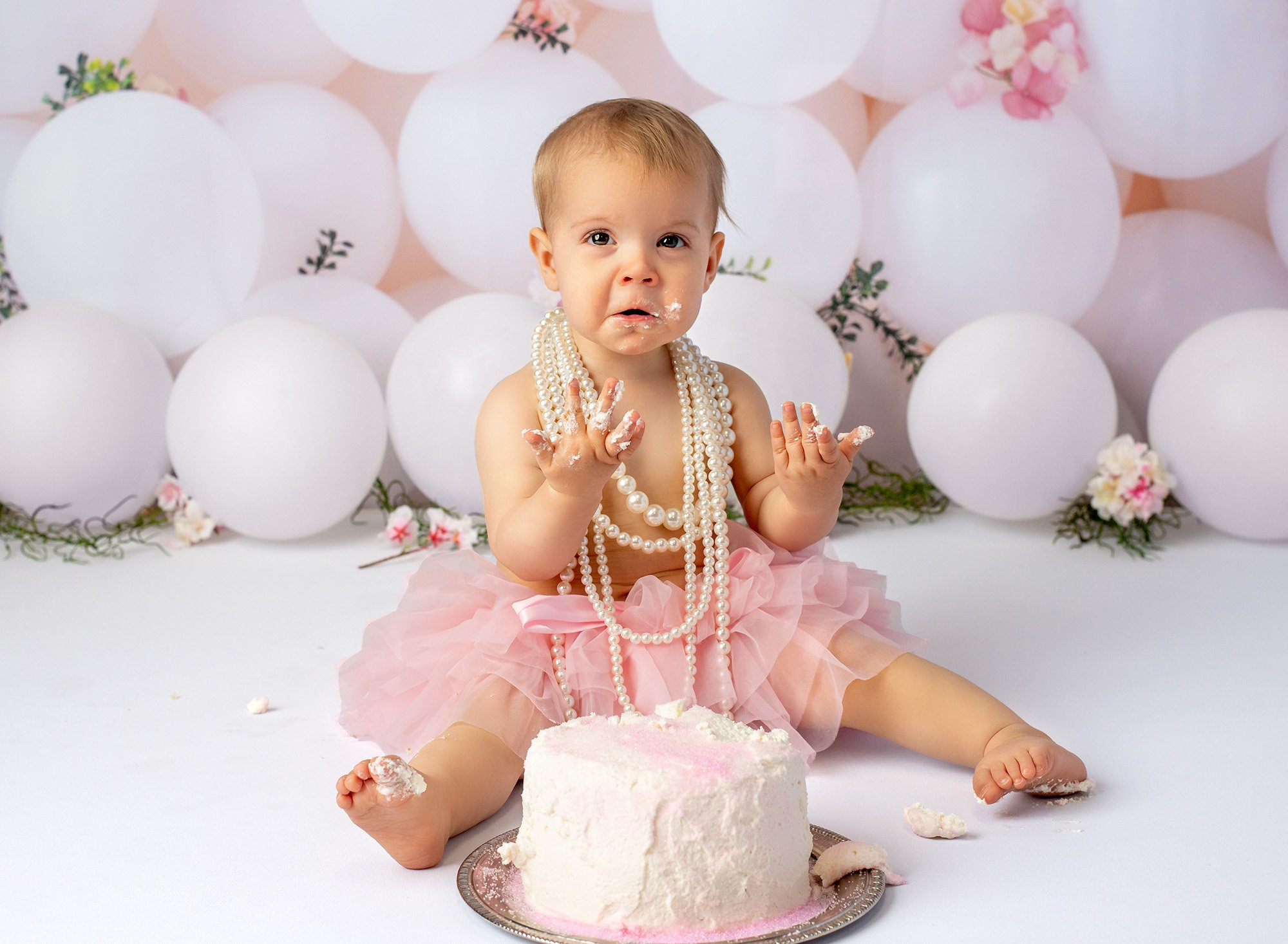 baby girl wearing layered pearl necklace sitting in front of cake with frosting on hands with white balloons in background