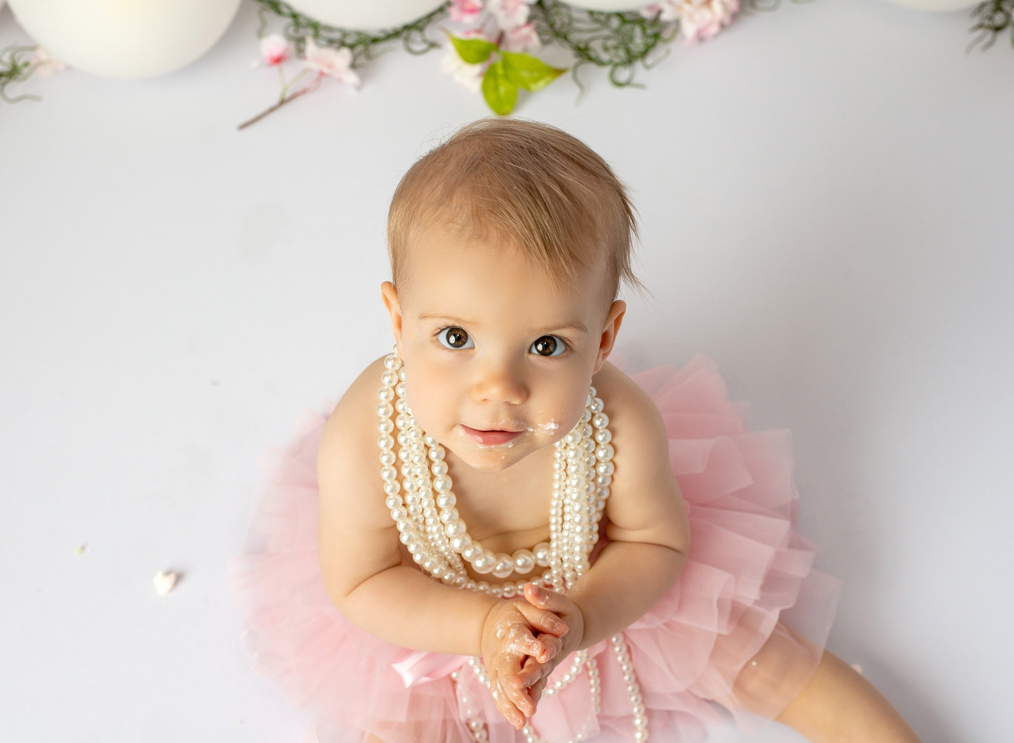 brown eyed baby girl wearing layered pearl necklace and pink tutu with cake frosting smeared on cheek and hands