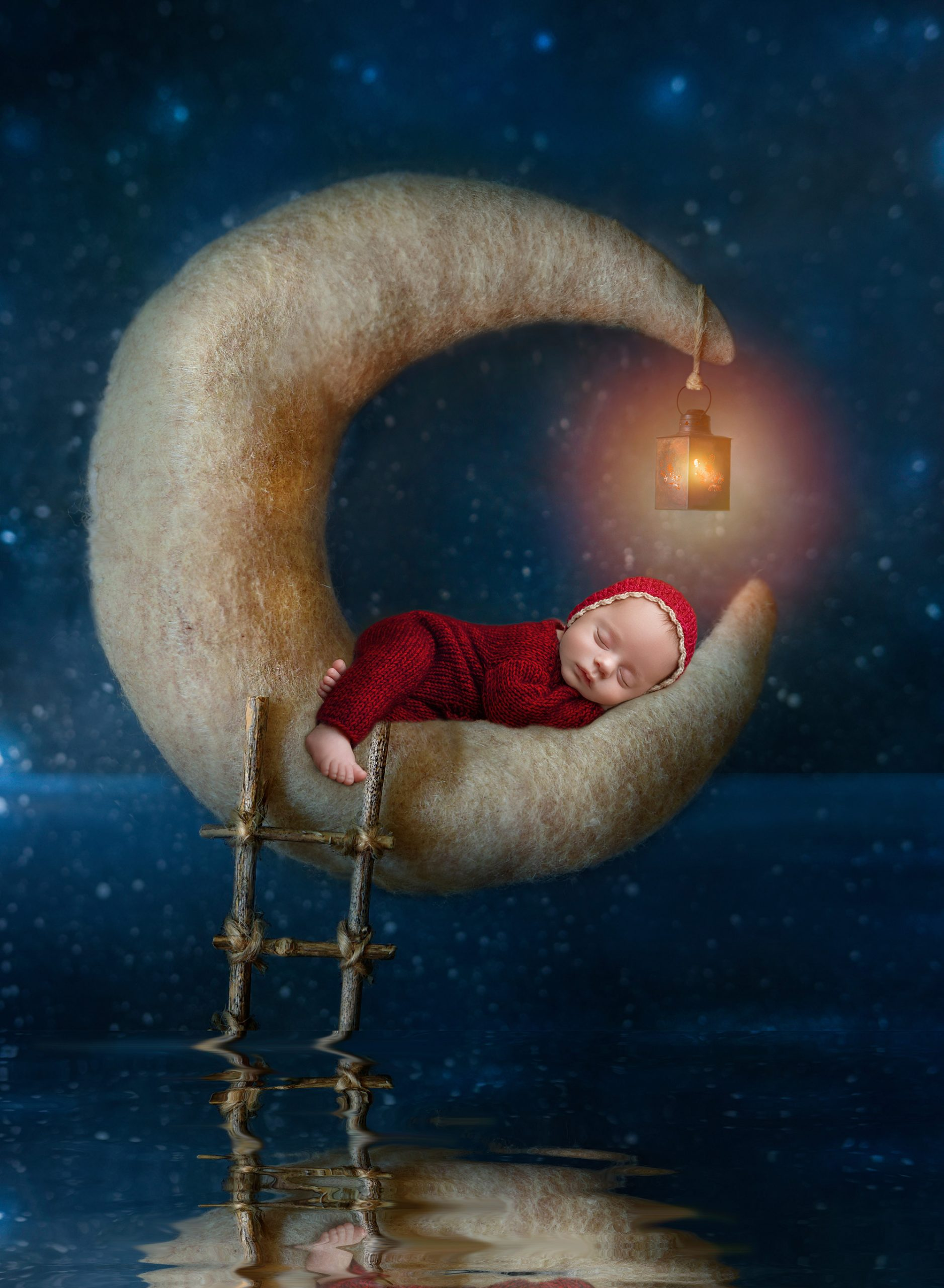 award winning newborn photography newborn baby boy dressed in red asleep on a crescent moon shadowing the water on a starry background