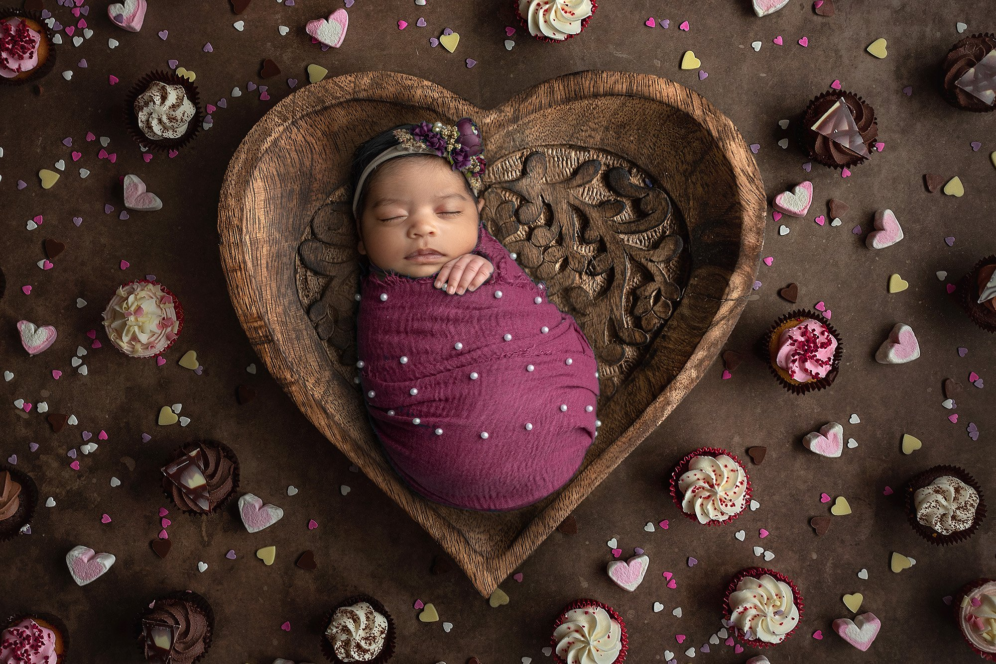 sleeping newborn baby girl swaddled in magenta wrap with pearls wearing purple floral headband laying in wooden heart bowl surrounded by cupcakes and heart candies