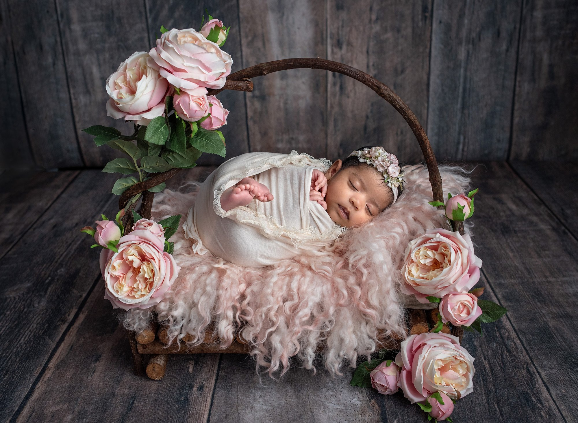 newborn baby girl swaddled in lace wrap sleeping on top of rustic wooden bed with pink fuzzy blanket surrounded by pink flowers on wooden background