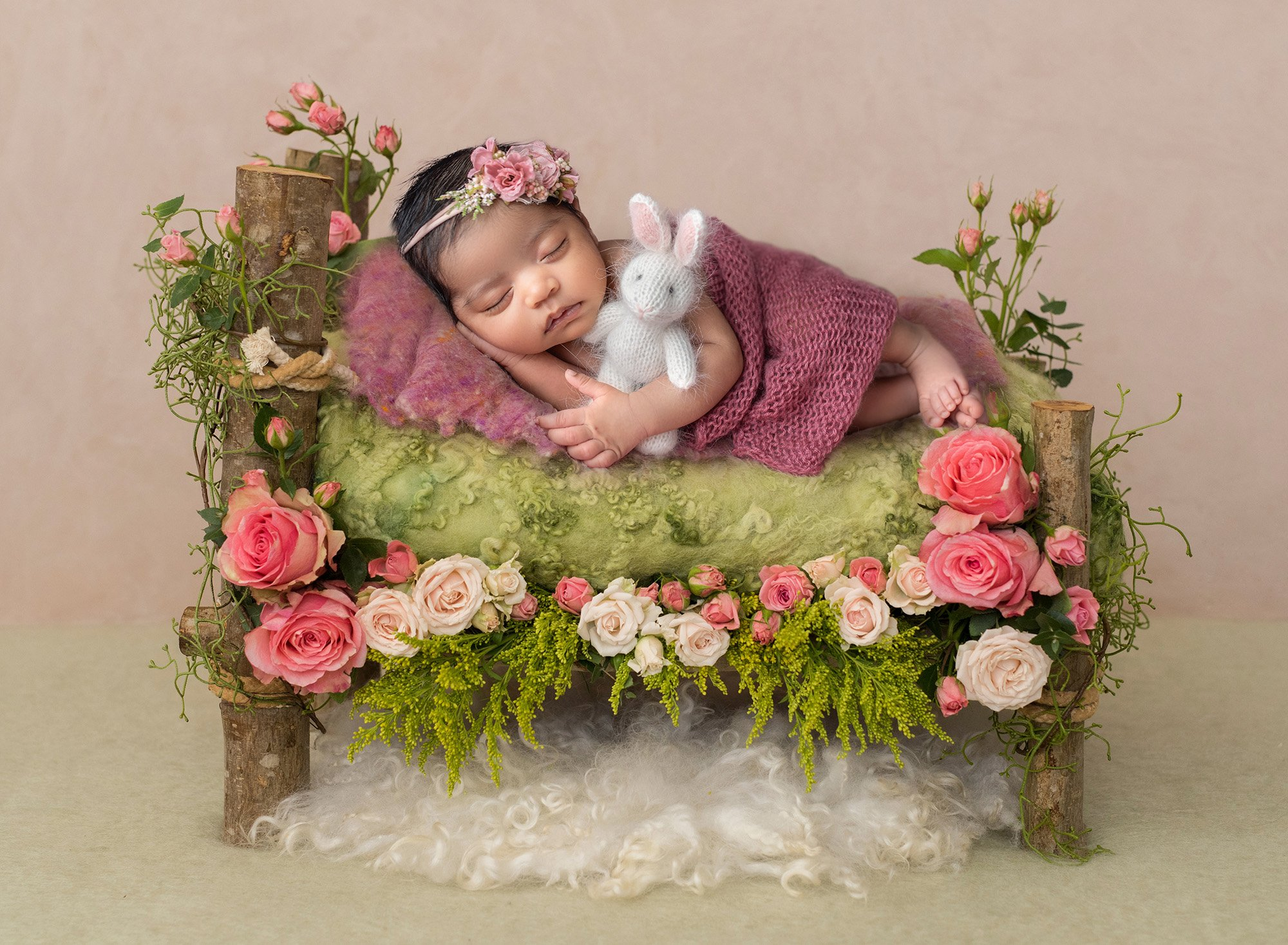 newborn baby girl sound asleep on wooden bed draped in mauve sweater wrap holding stuffed bunny surrounded by pink flowers and greenery atop a fuzzy blanket