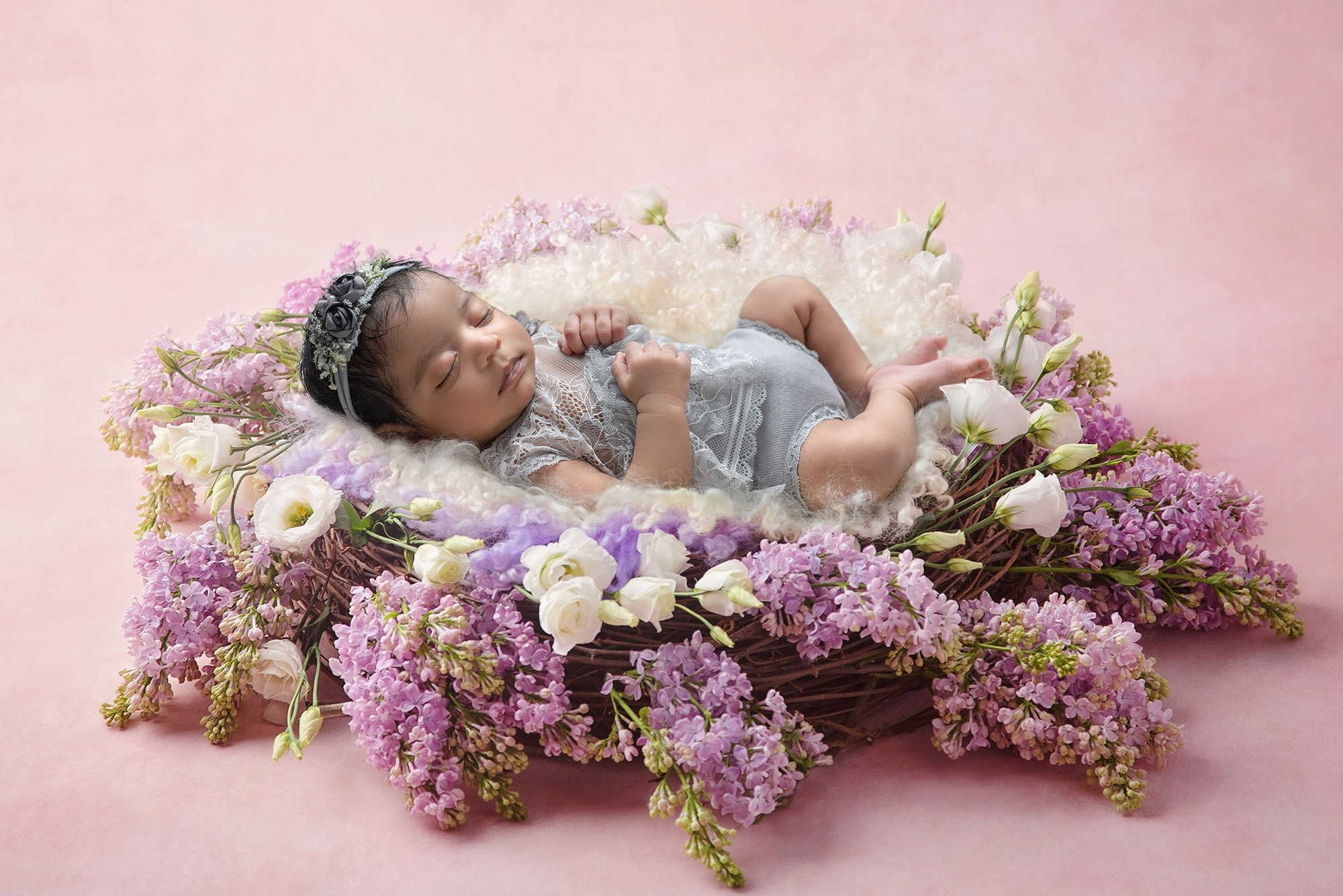 newborn baby girl in laced grey dress sound asleep on top of a purple and white floral wreath with fuzzy purple and white blankets on pink background