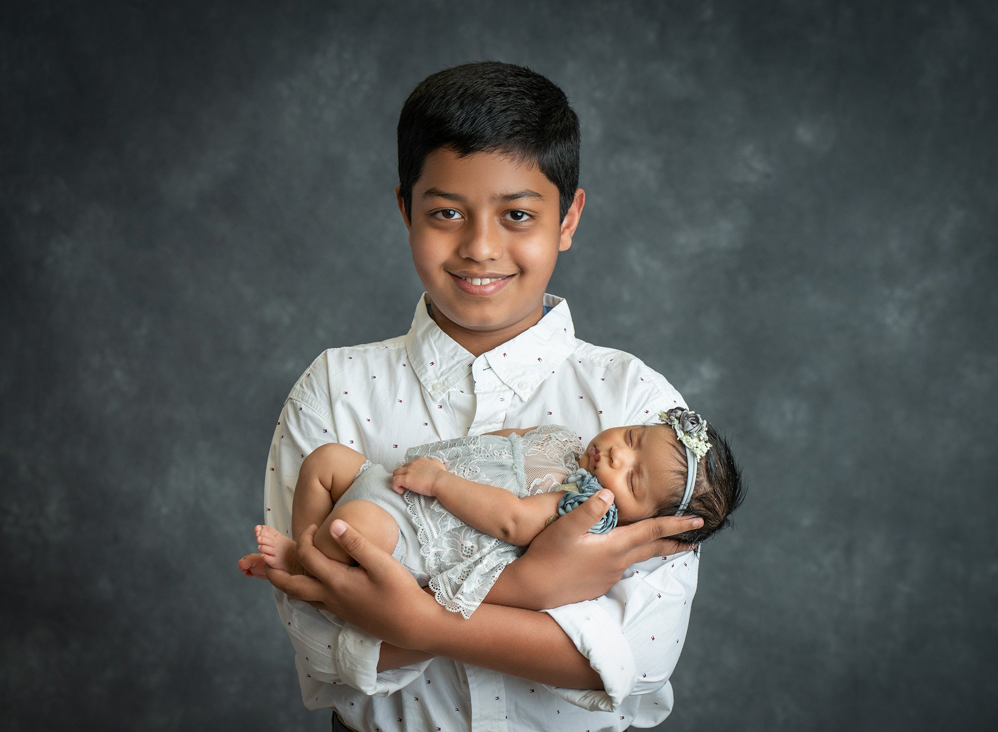 older brother proud to be holding asleep newborn baby sister dressed in a grey floral dress