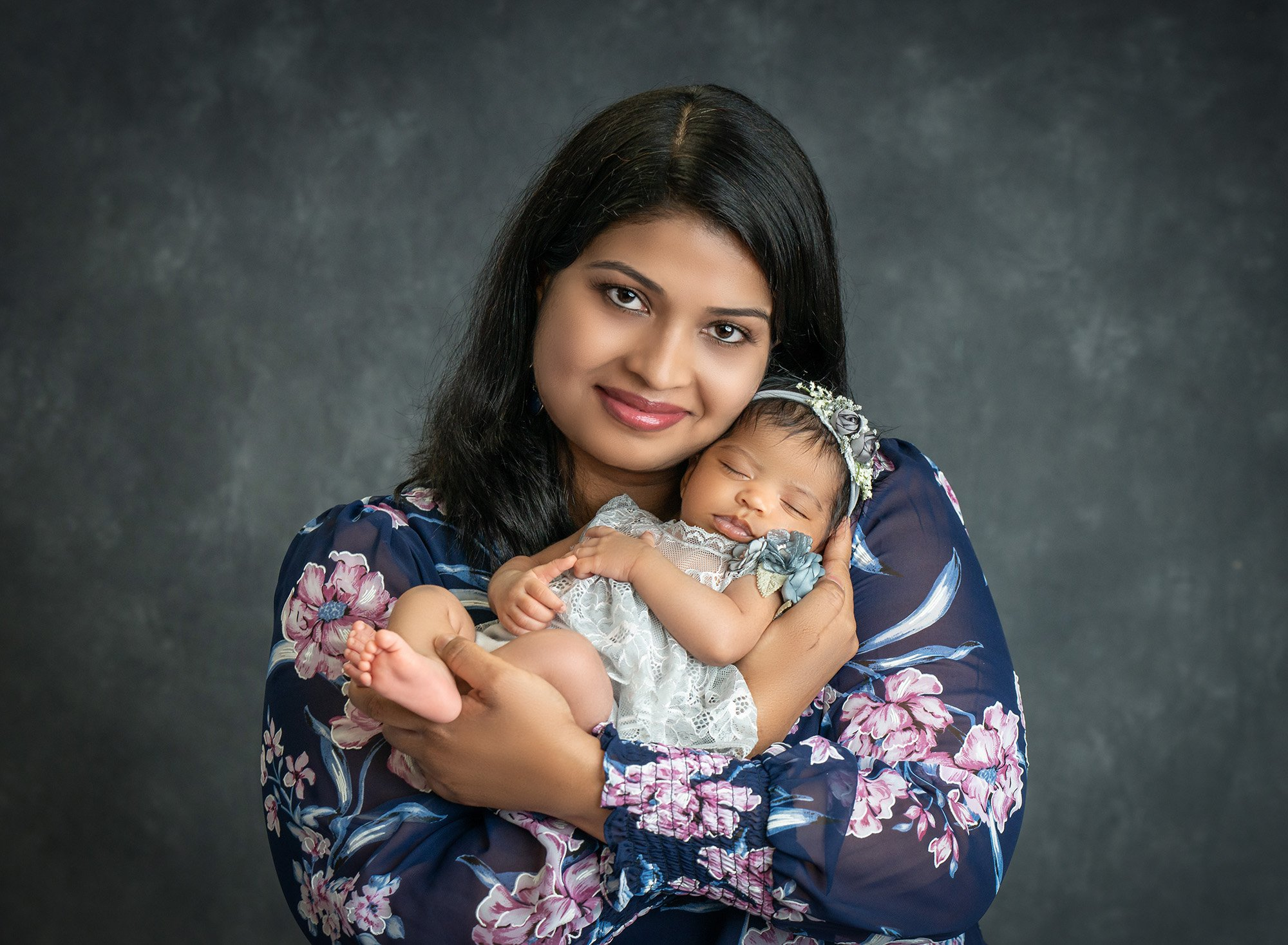 new mom cradling newborn baby girl in grey floral dress close to her chest