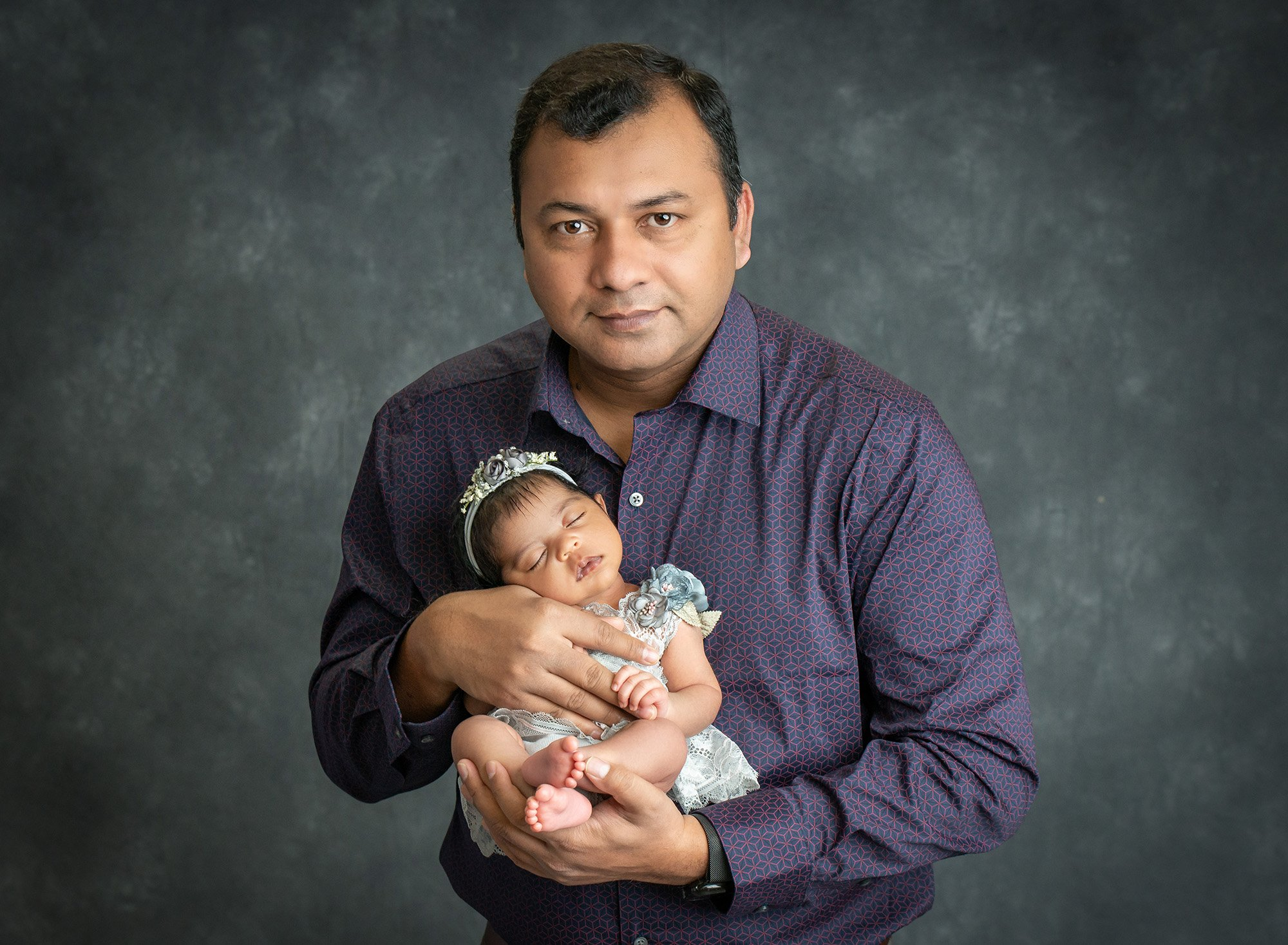 new dad holding sweet newborn baby girl dressed in a floral grey dress and headband on grey background