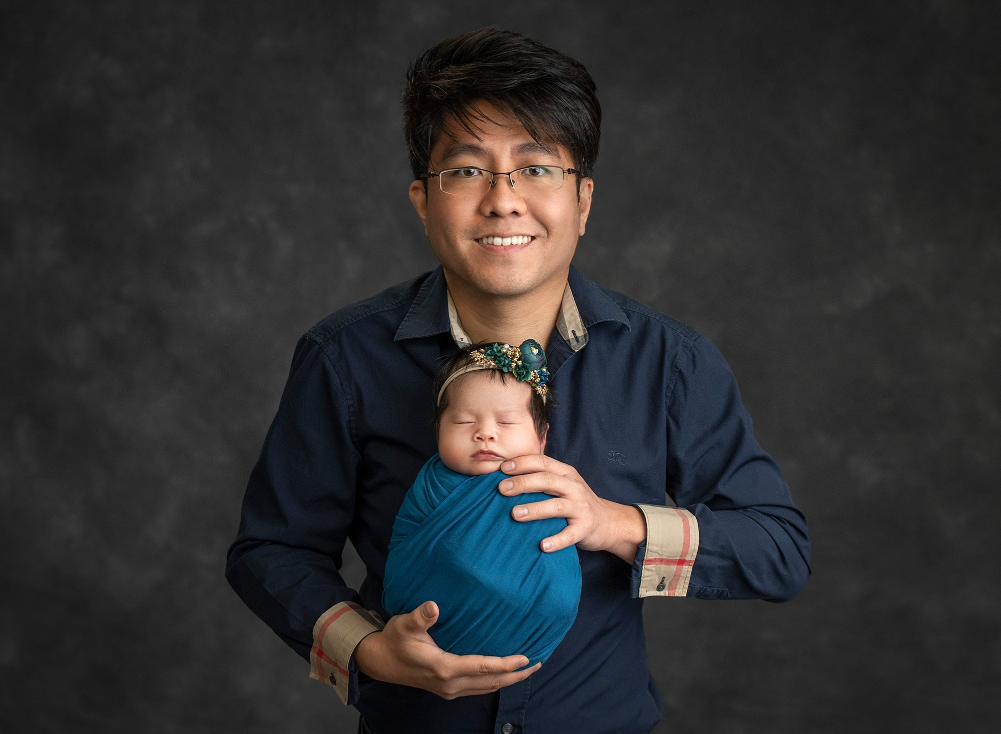 new dad wearing Burberry button up holding newborn baby girl swaddled in dark teal wrap wearing teal floral headband on dark grey background