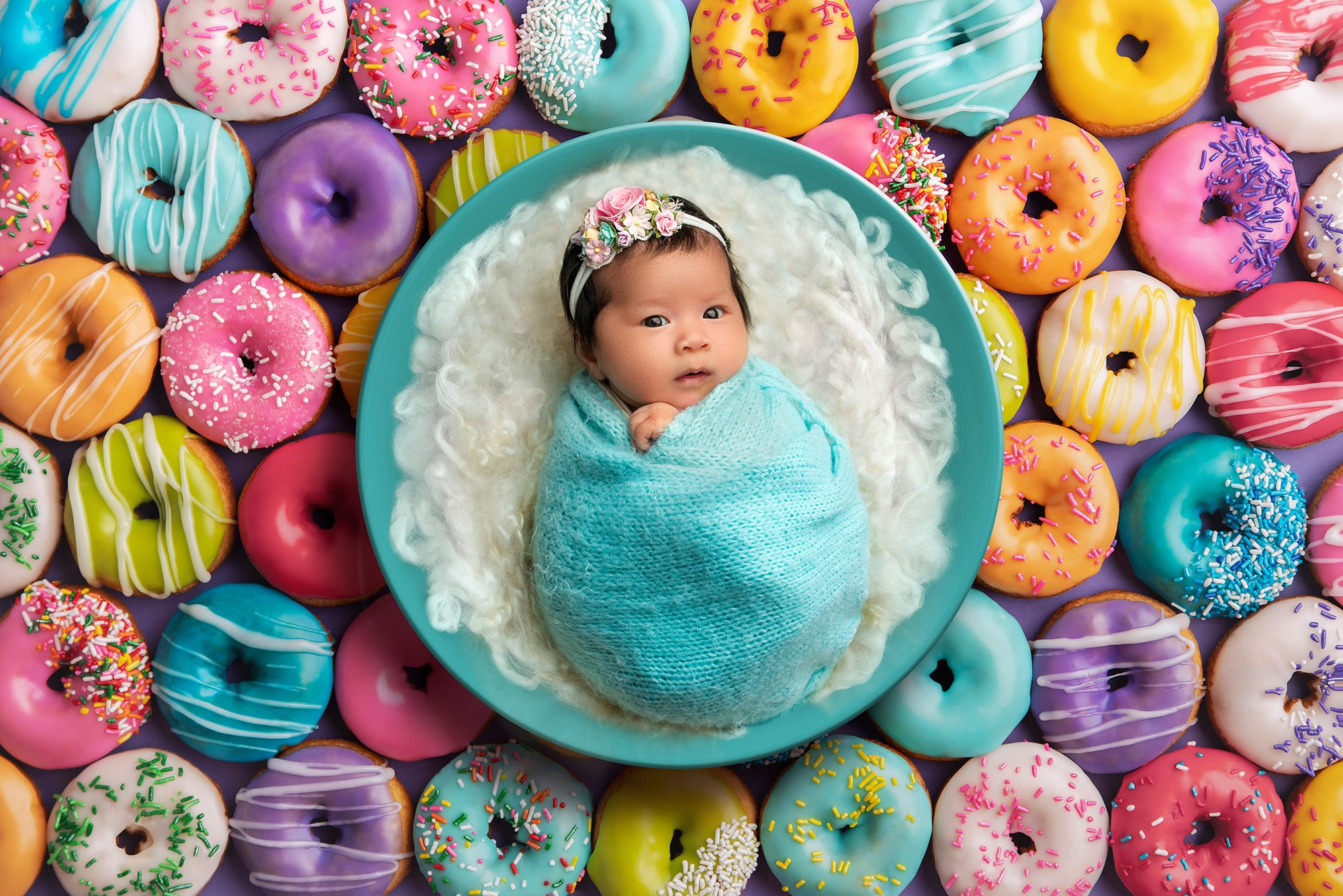vibrant newborn photo awake newborn baby girl swaddled in an aqua sweater wrap laying in aqua bowl with fuzzy white blanket on a donut background