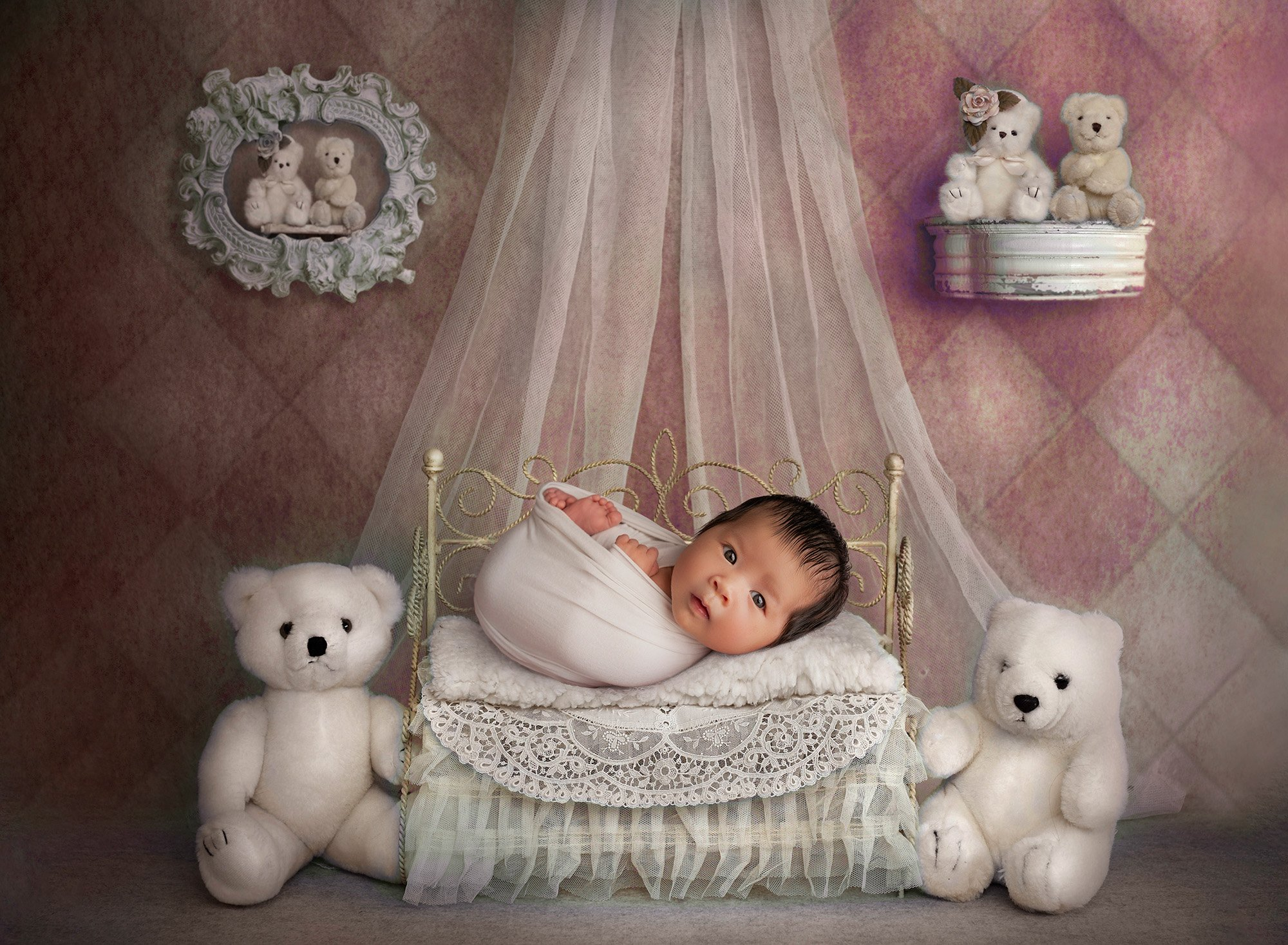 awake newborn baby girl laying in miniature princess bed surrounded by stuffed animal bears on a pink diamond background