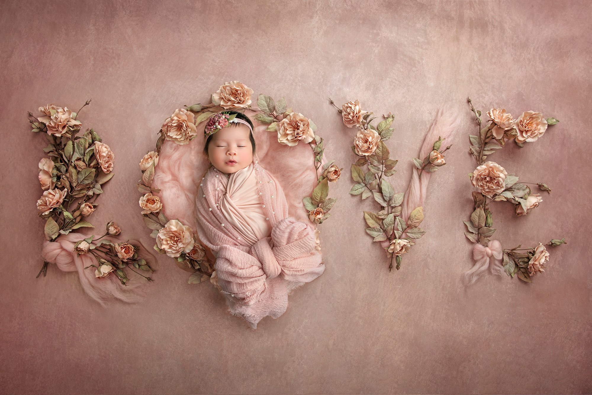 sweet newborn baby girl asleep on a pink background spelling out the word LOVE in flowers and bows