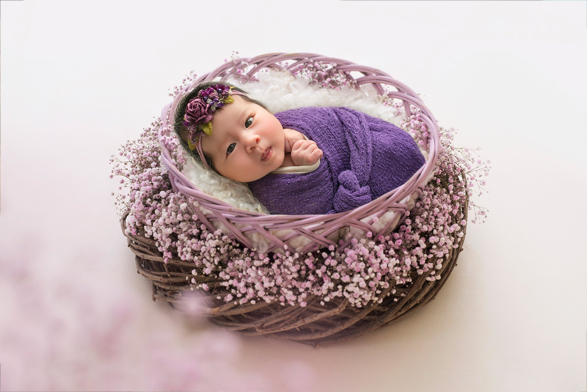 vibrant newborn photo month old baby girl swaddled in purple wrap in a lavender nest looking at the camera with eyes open best time to take newborn photos