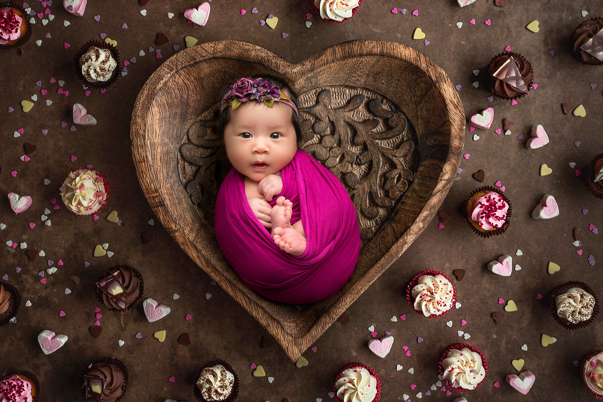 awake newborn baby girl swaddled in magenta wrap wearing purple floral headband laying in wooden heart bowl surrounded by cupcakes and heart candies