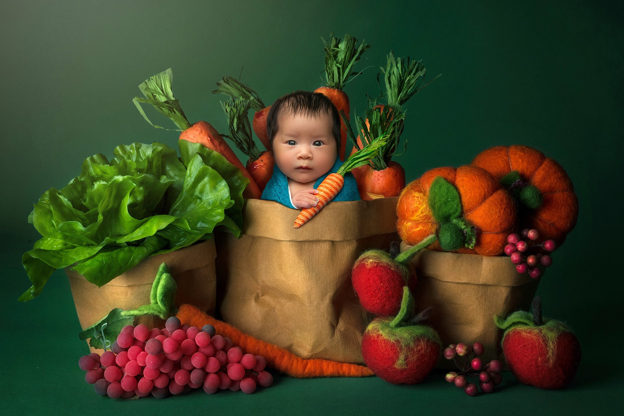 vibrant newborn photo newborn baby girl sitting in brown paper bag holding carrot surrounded by felt vegetables and fruit on a green background